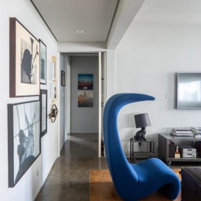 decoração sala tv com poltrona curva azul e abajur cachorro preto