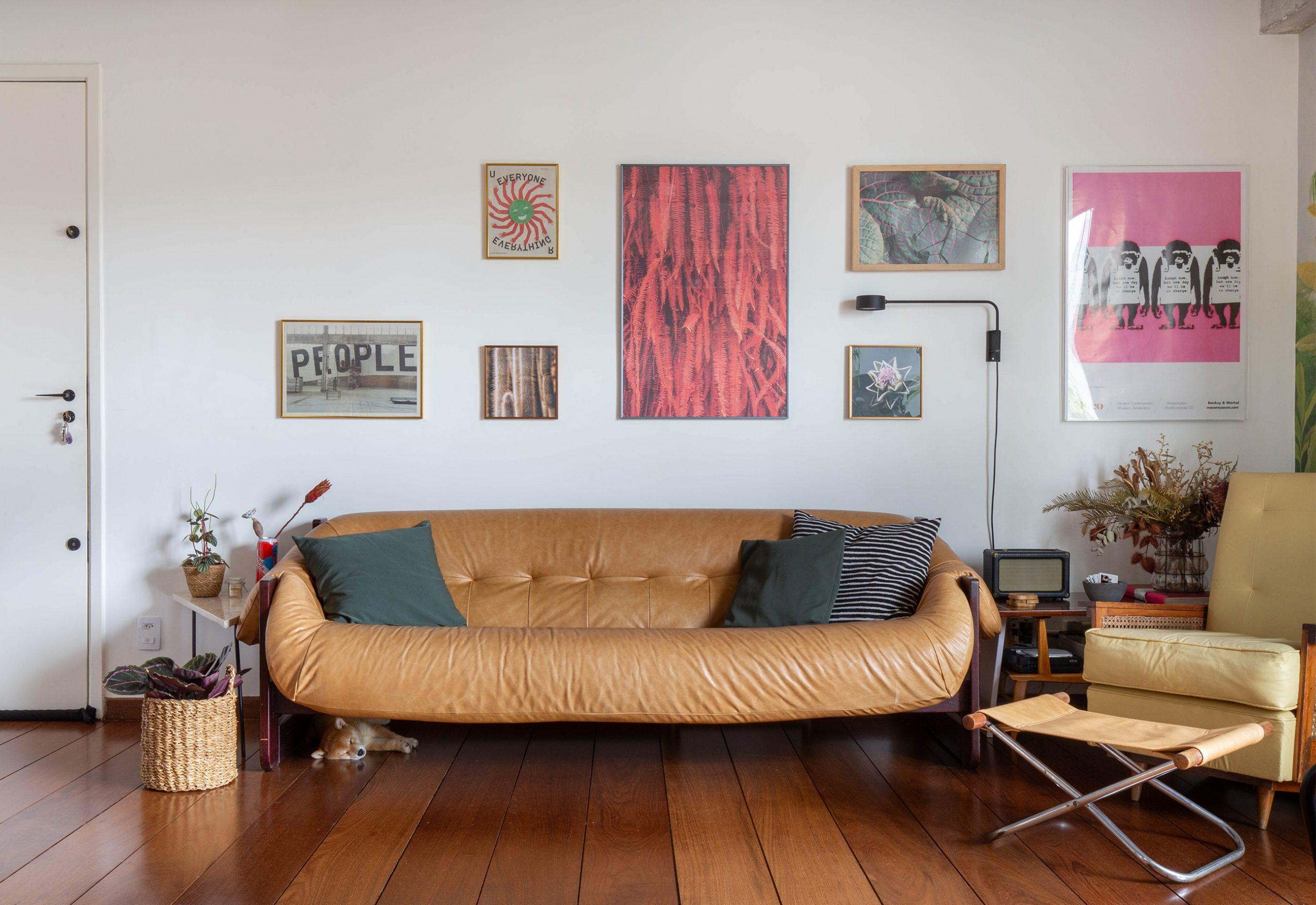 decoração sala com sofá de couro cesto de palha e quadros na parede