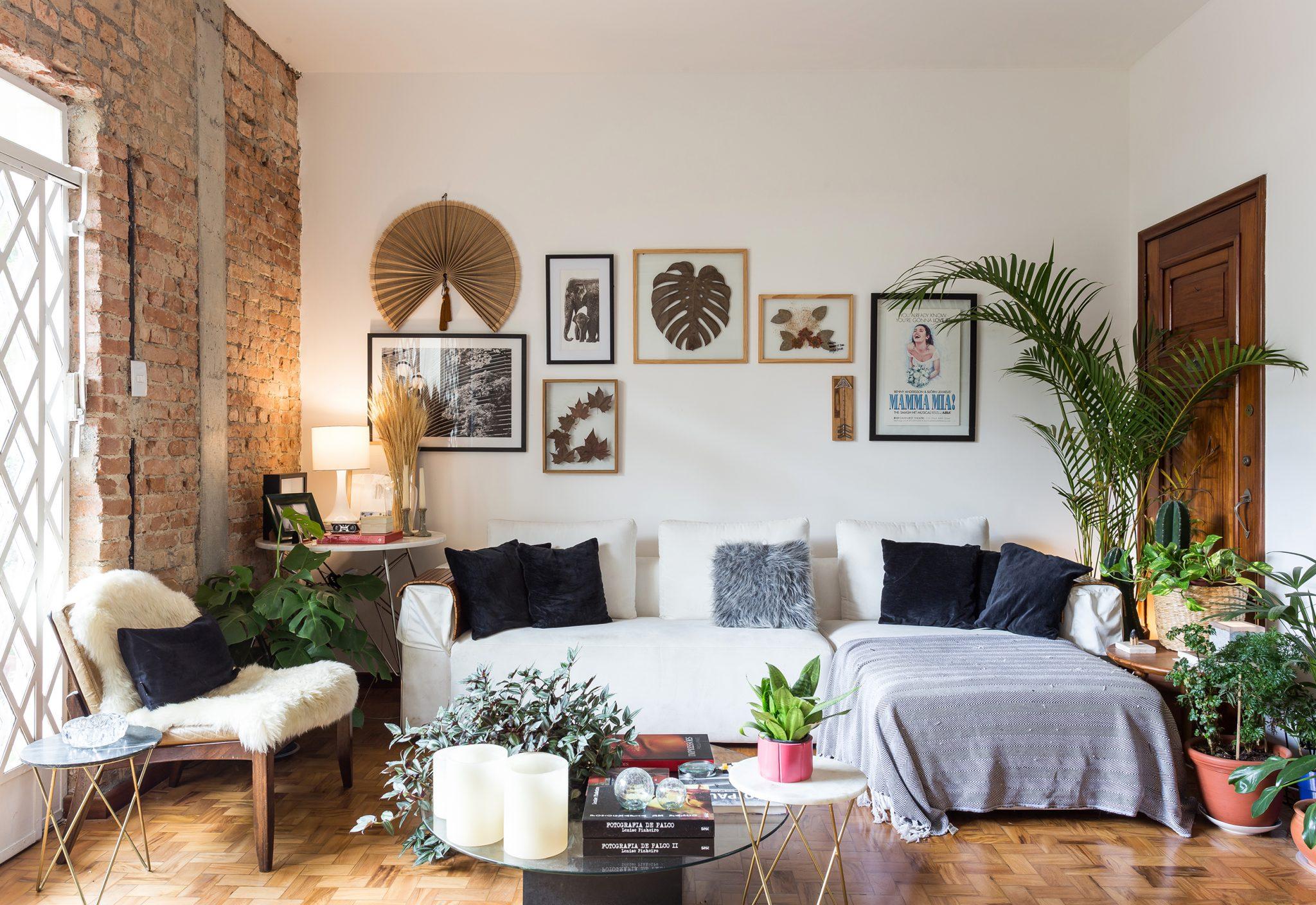 decoração sala com parede de tijolos muitas plantas e sofá branco
