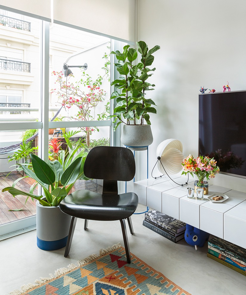 decoração de sala com aparador de azulejo e muitas plantas