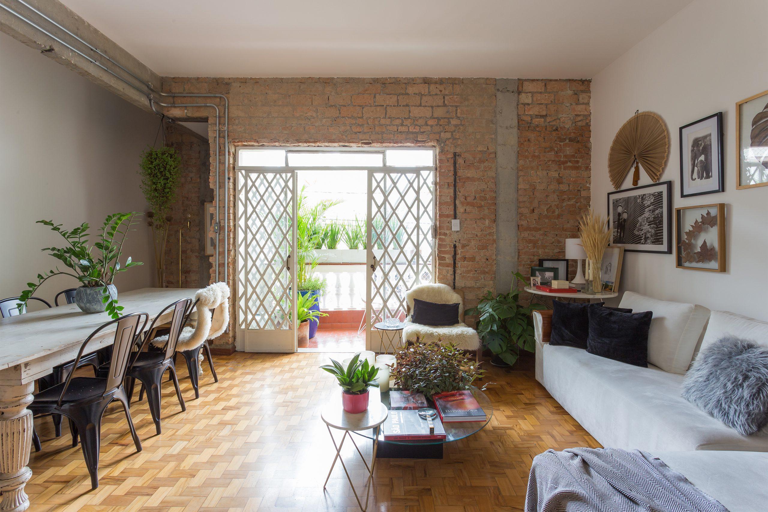 decoração sala com parede de tijolos mesa e sofá branco e plantas