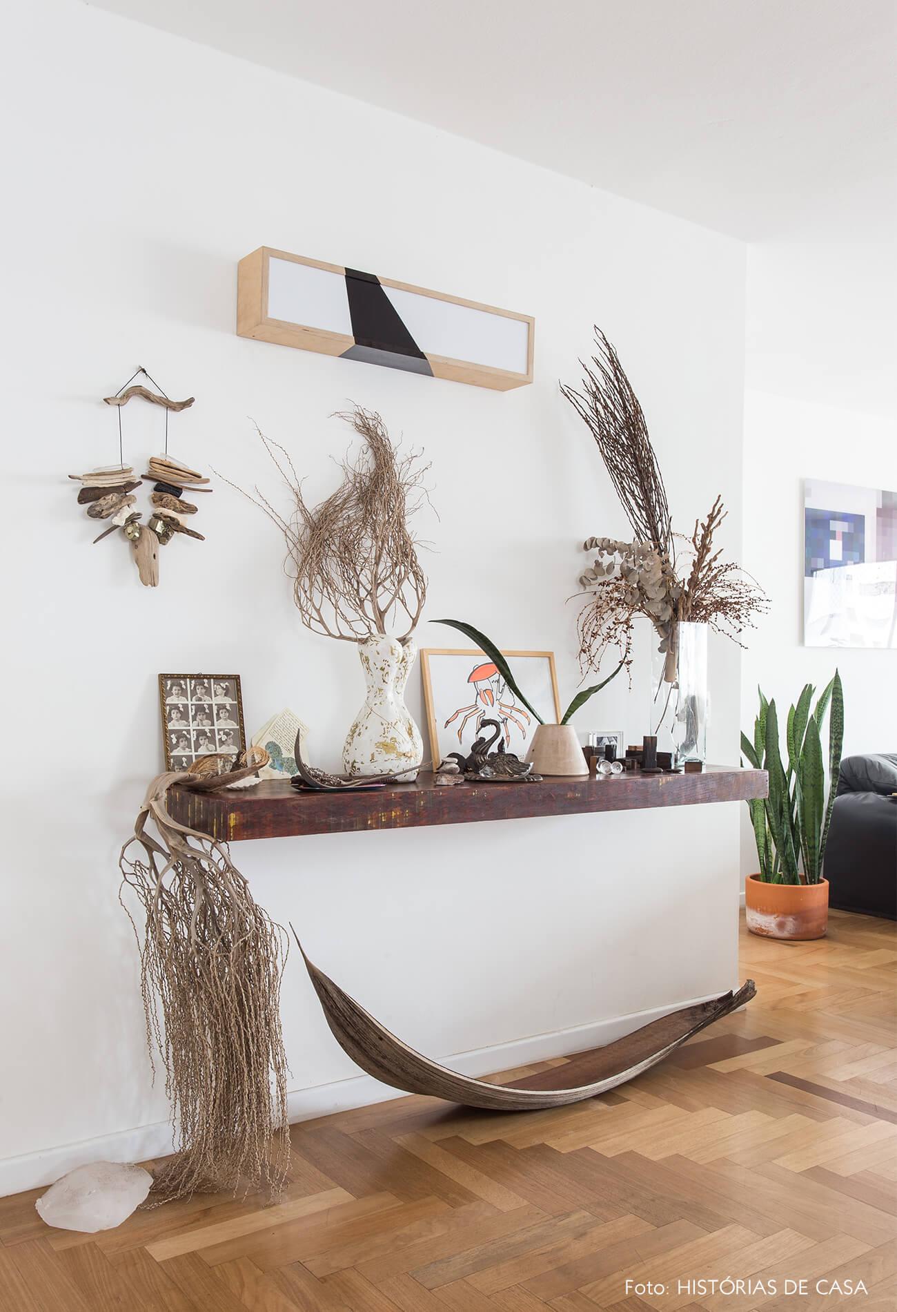 decoração hall com estante madeira e folhas secas
