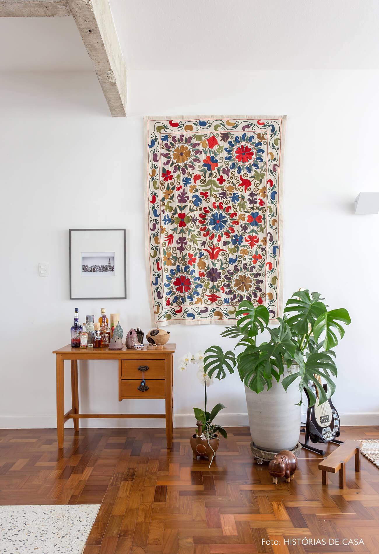 decoração sala com painel de tecido na parede, mesa de madeira e esturutra de concreto