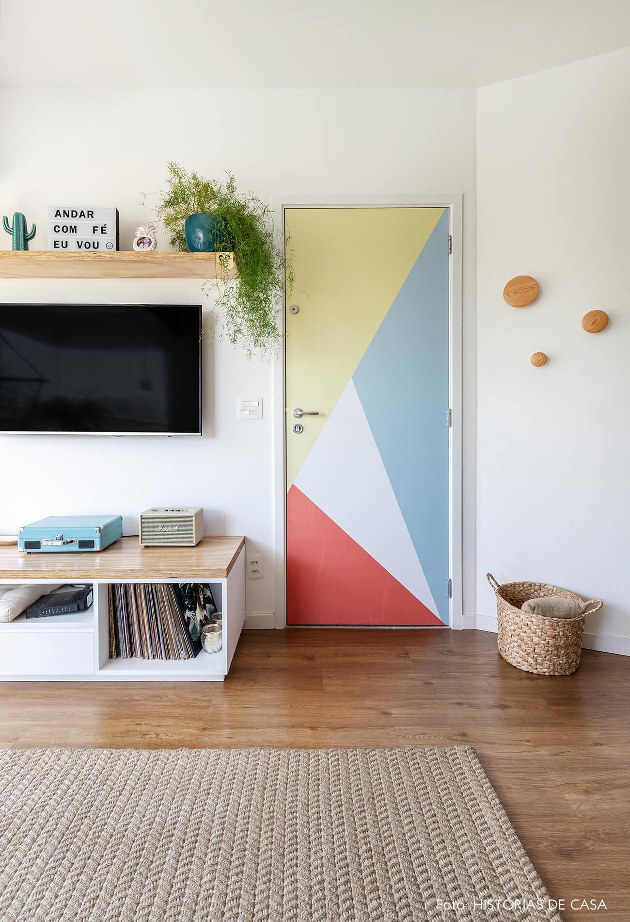 decoração sala com prateleiras de madeira e adesivo geometrico em porta