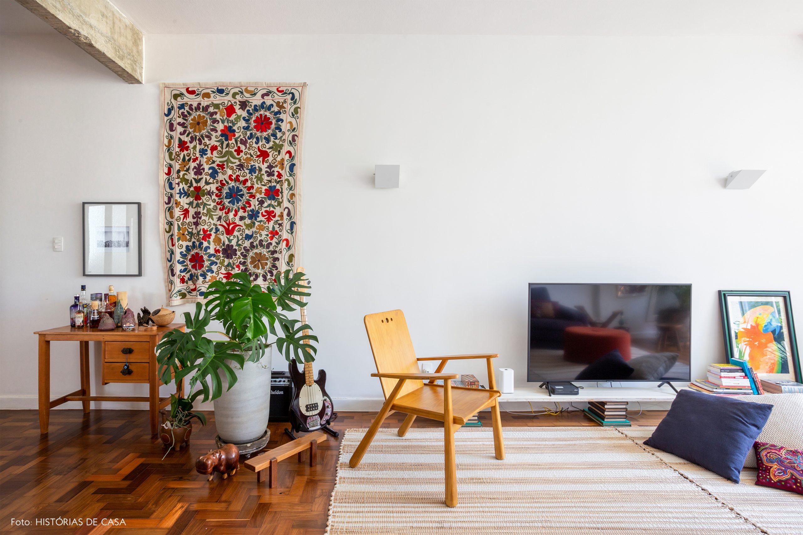 decoração sala com painel de tecido na parede, cadeira de madeira e almofadas no chão