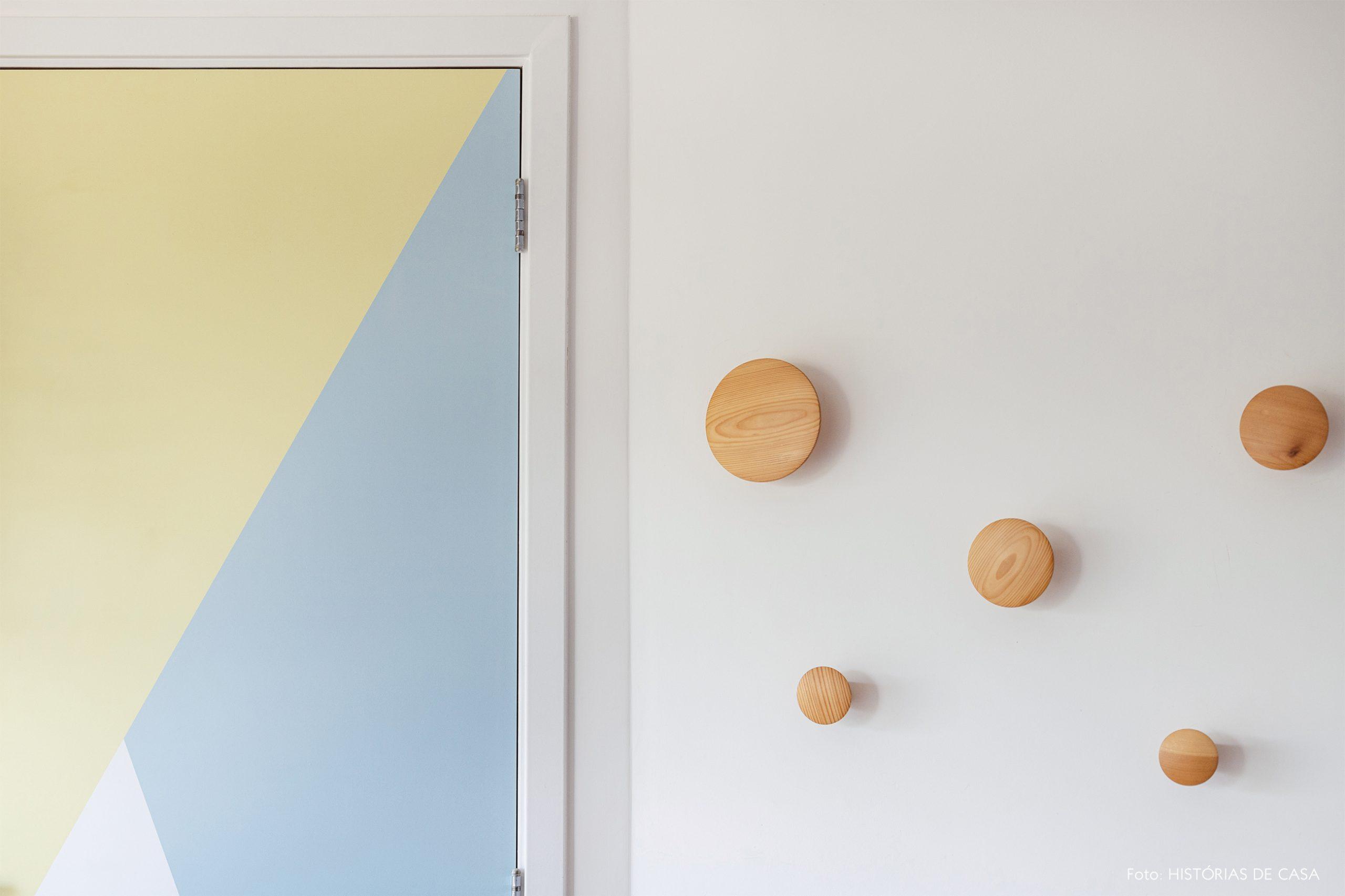 decoração porta com adesivo geométrico e ganchos de madeira