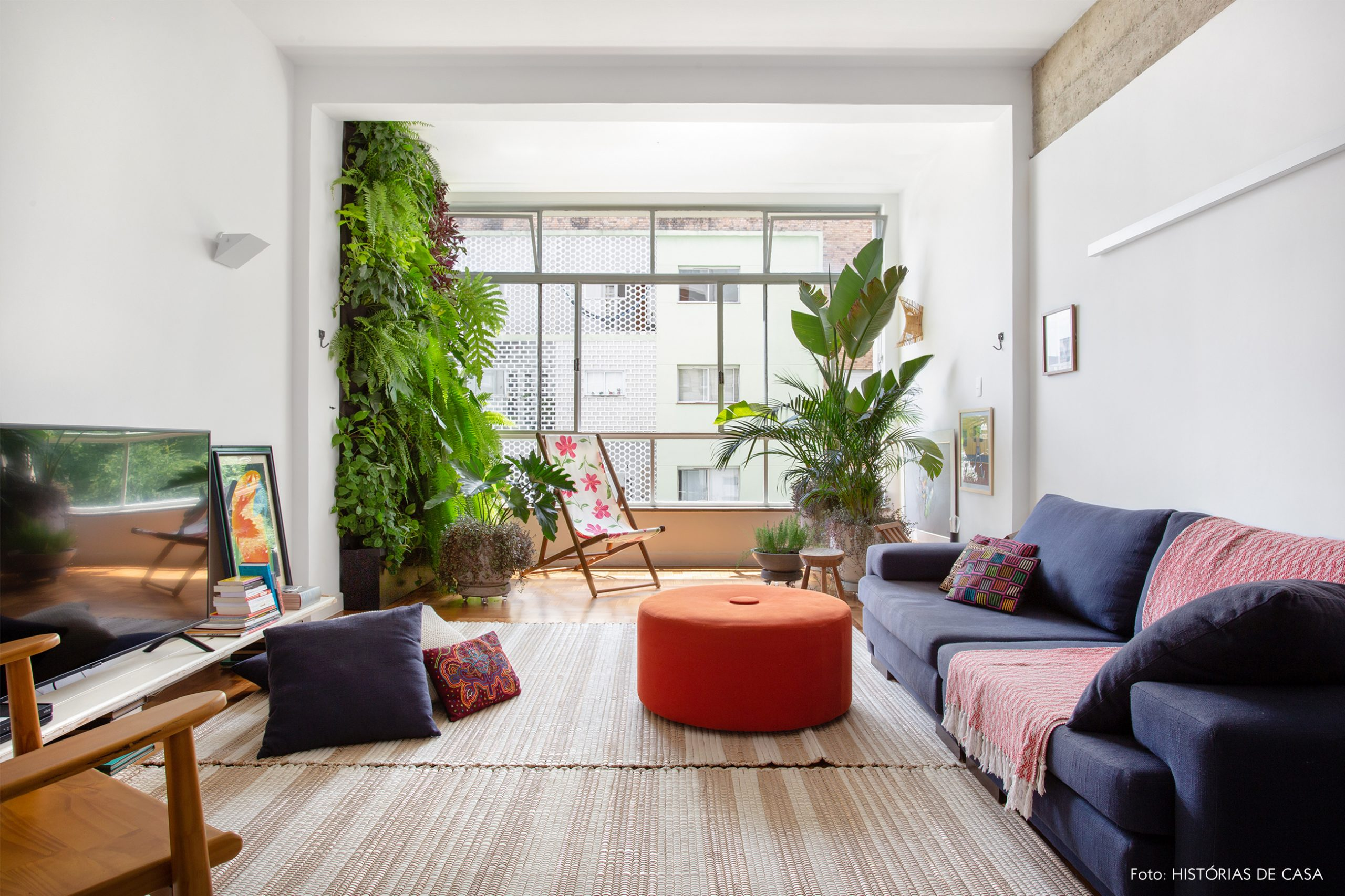 decoração sala com muitas plantas, pufes coloridos e cadeira de madeira e tecido