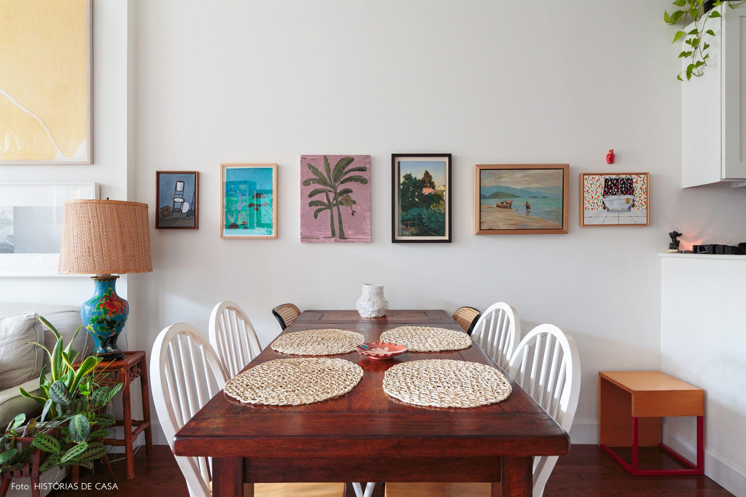 ap decoração sala jantar com mesa de madeira e muitos quadros