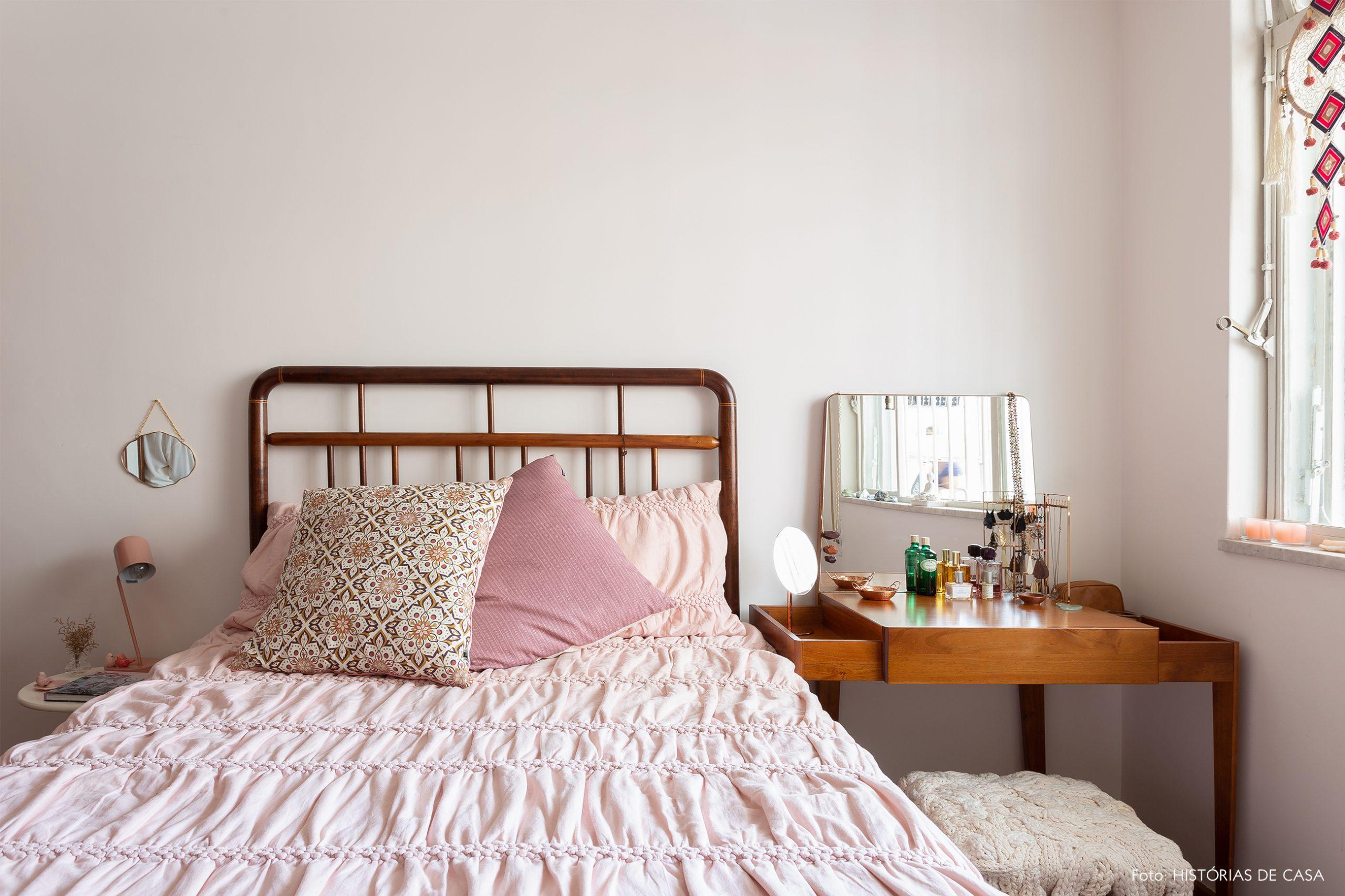 decoração quarto com parede rosa claro e cama de madeira escura