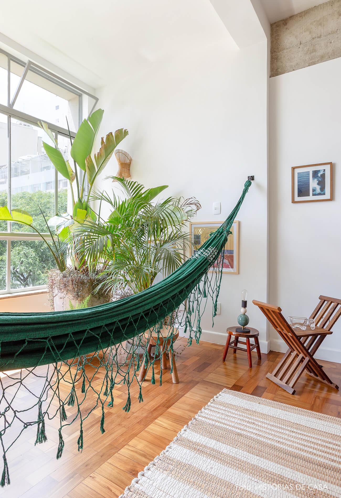decoração sala com muitas plantas, rede e banquinhos de madeira