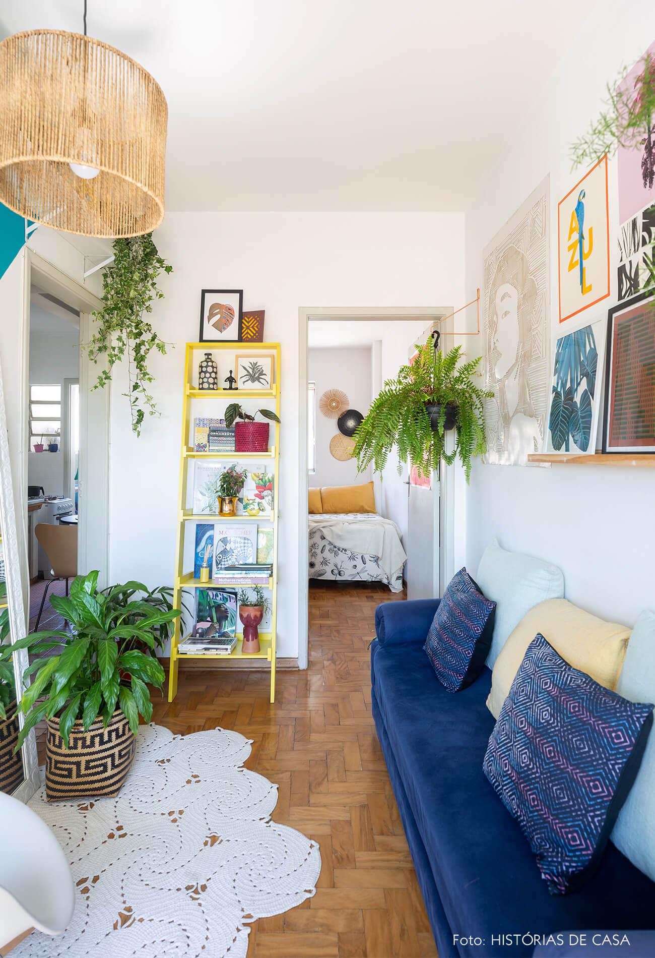 decoração sala com sofá azul, estante escada amarela e cesto
