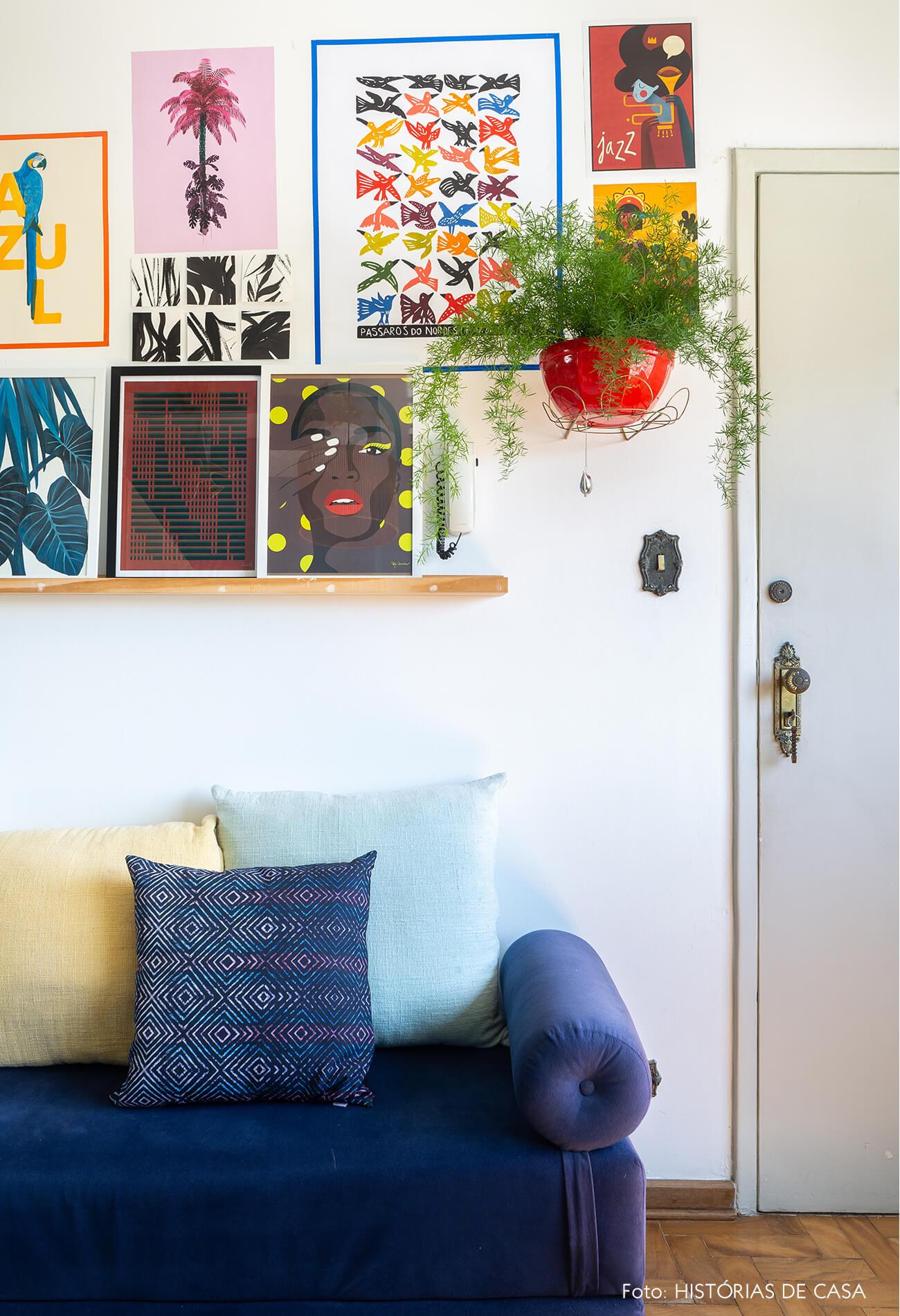 decoração sala com sofá azul e muitos quadros