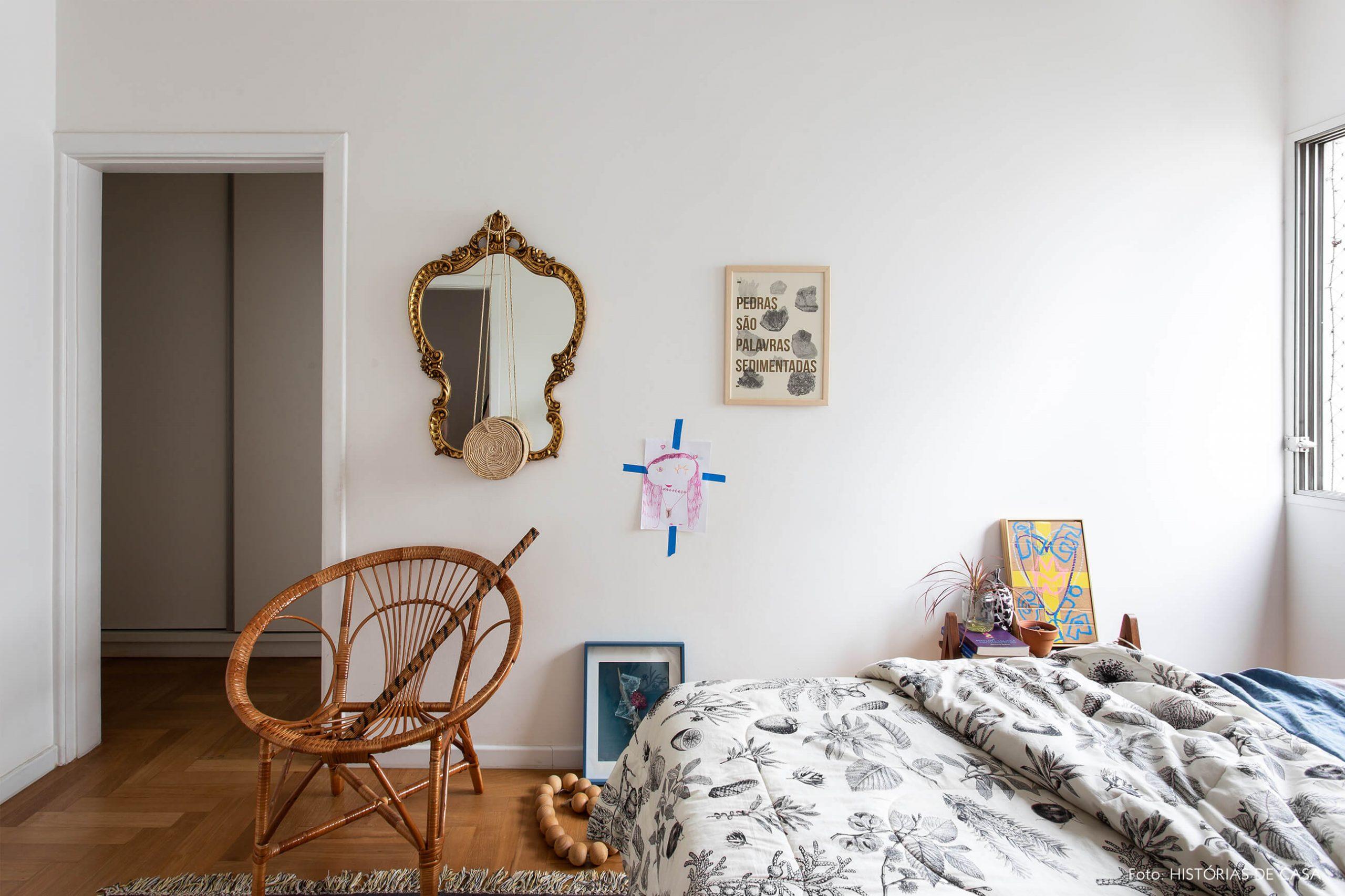 decoração quarto com espelho de moldura dourada e poltrona de madeira