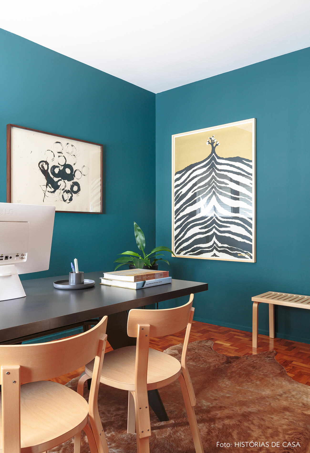 decoração home office de parede azul com cadeiras de madeira e obras de arte