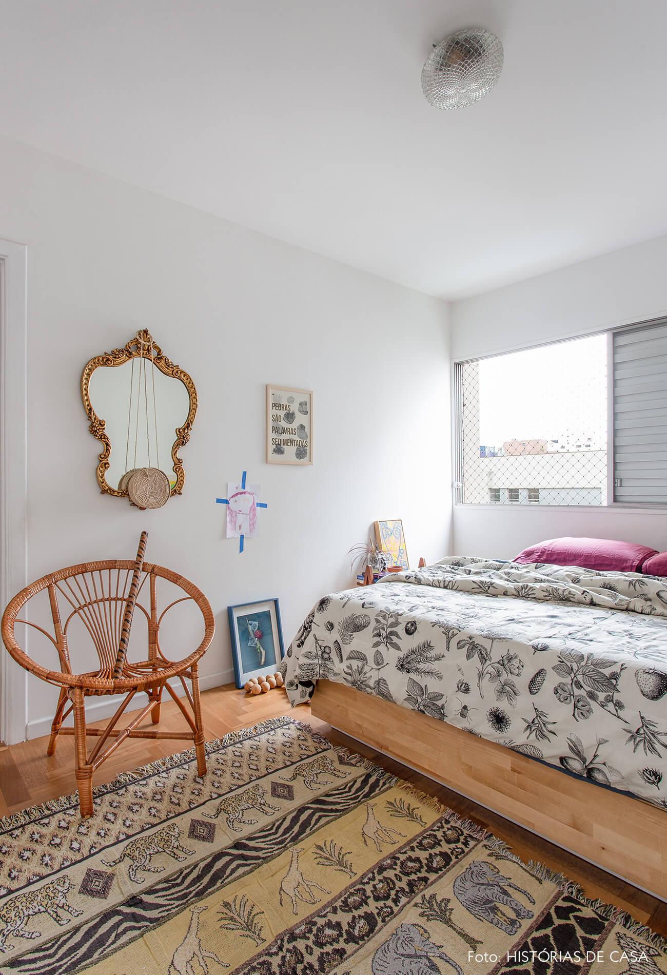 decoração quarto com poltrona de madeira espelho dourado e tapete estampado