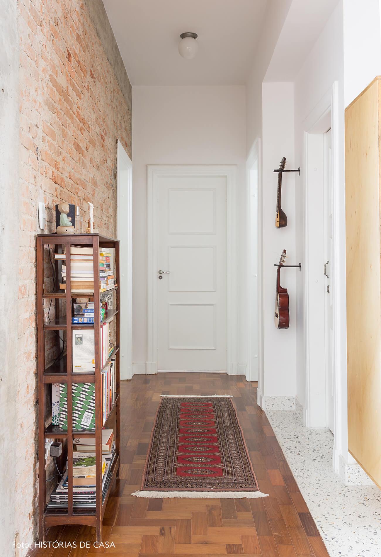 decoração corredor com parede de tijolinhos e chão de taco