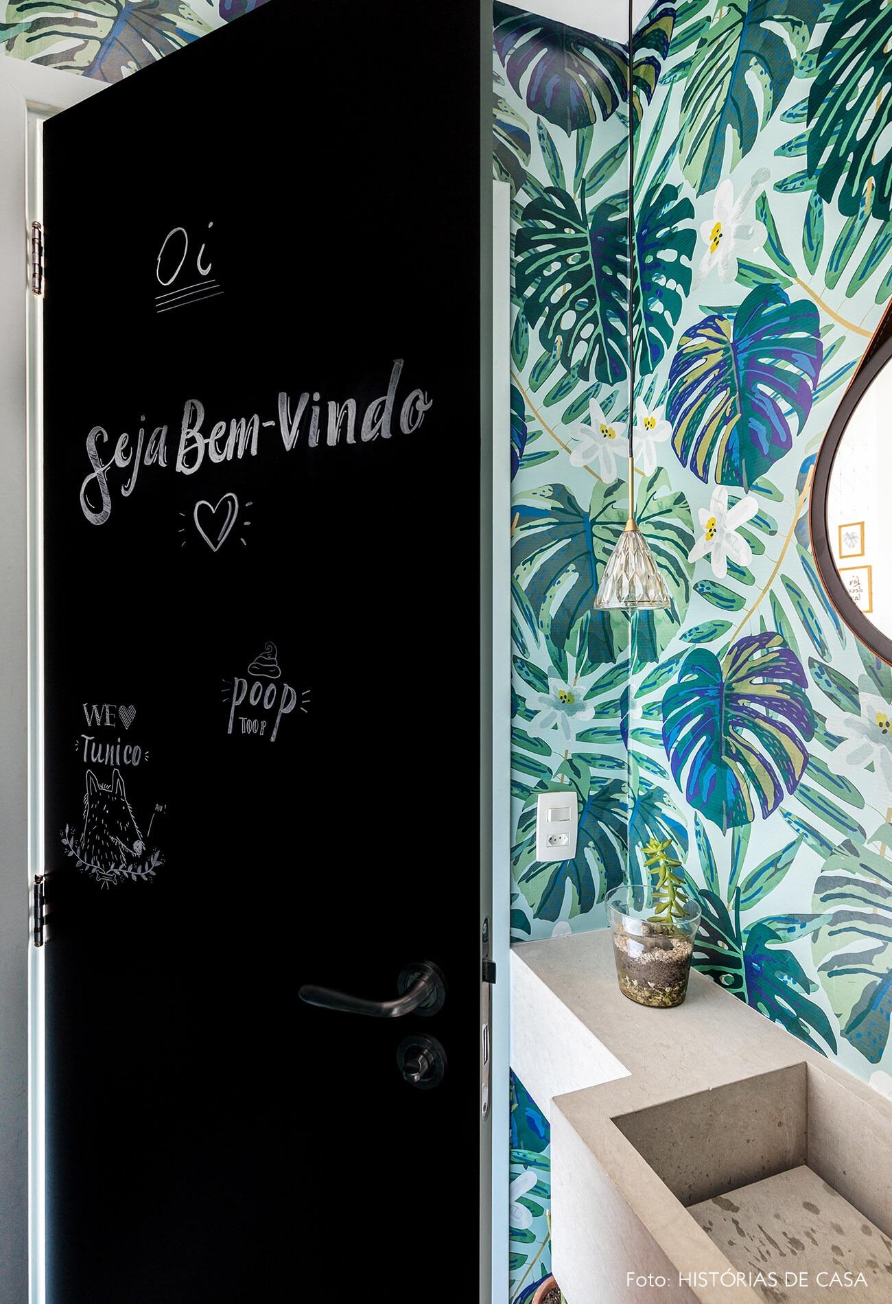 decoração banheiro com papel de parede estampado e adesivo lousa em porta
