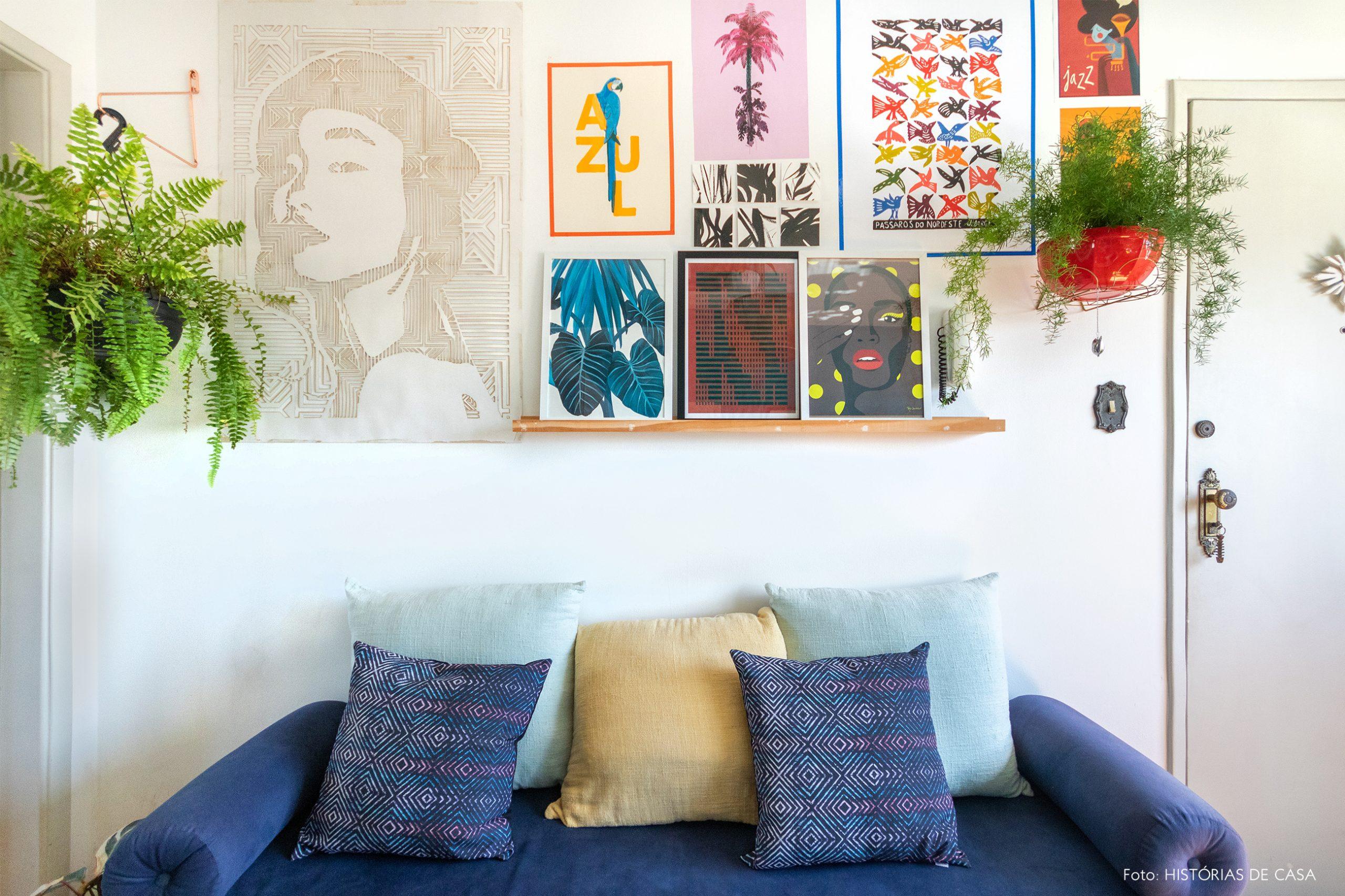 decoração sala com sofá azul, muitos qudros e plantas