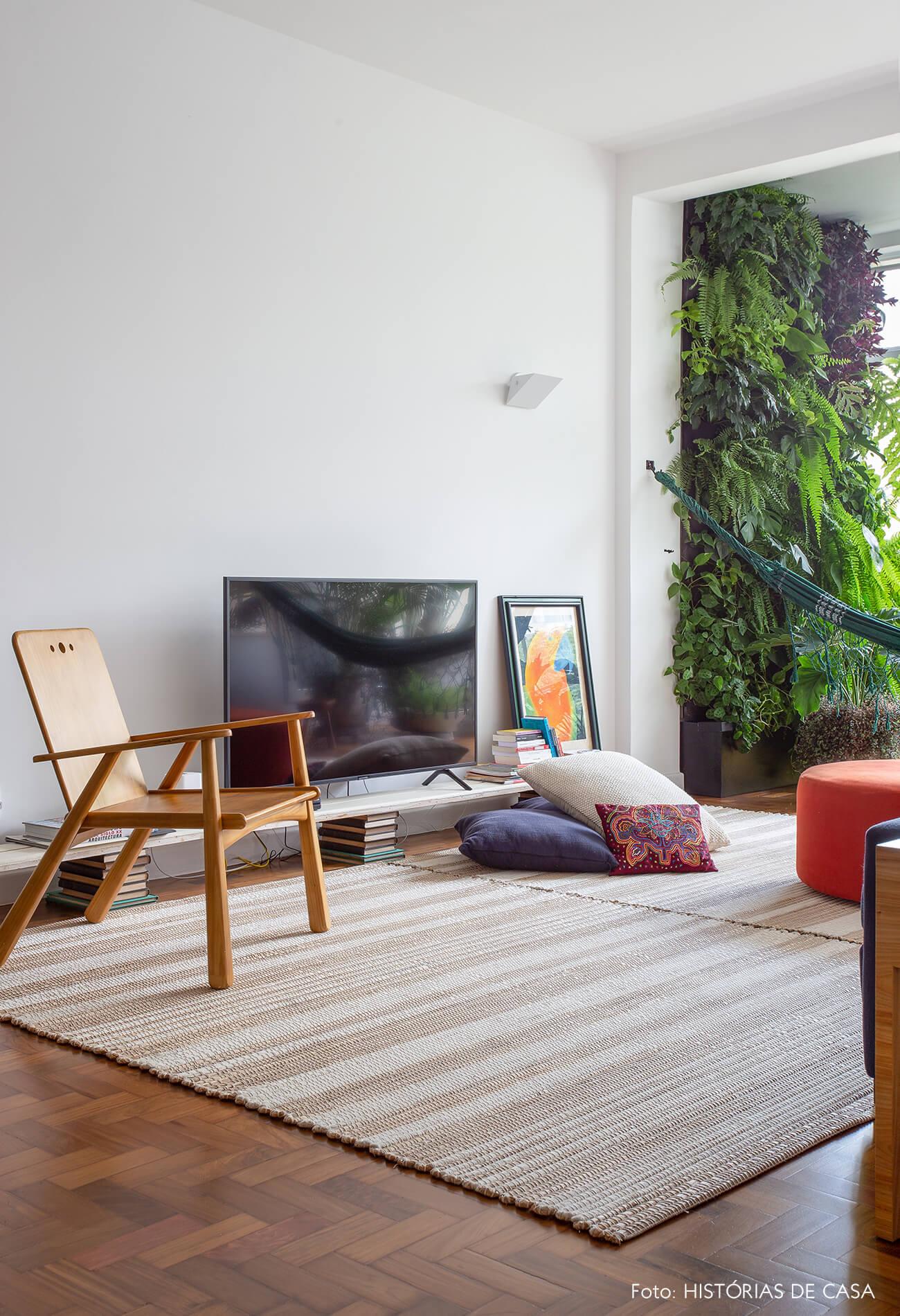 decoração sala com painel de plantas, cadeira de madeira e pufes coloridos