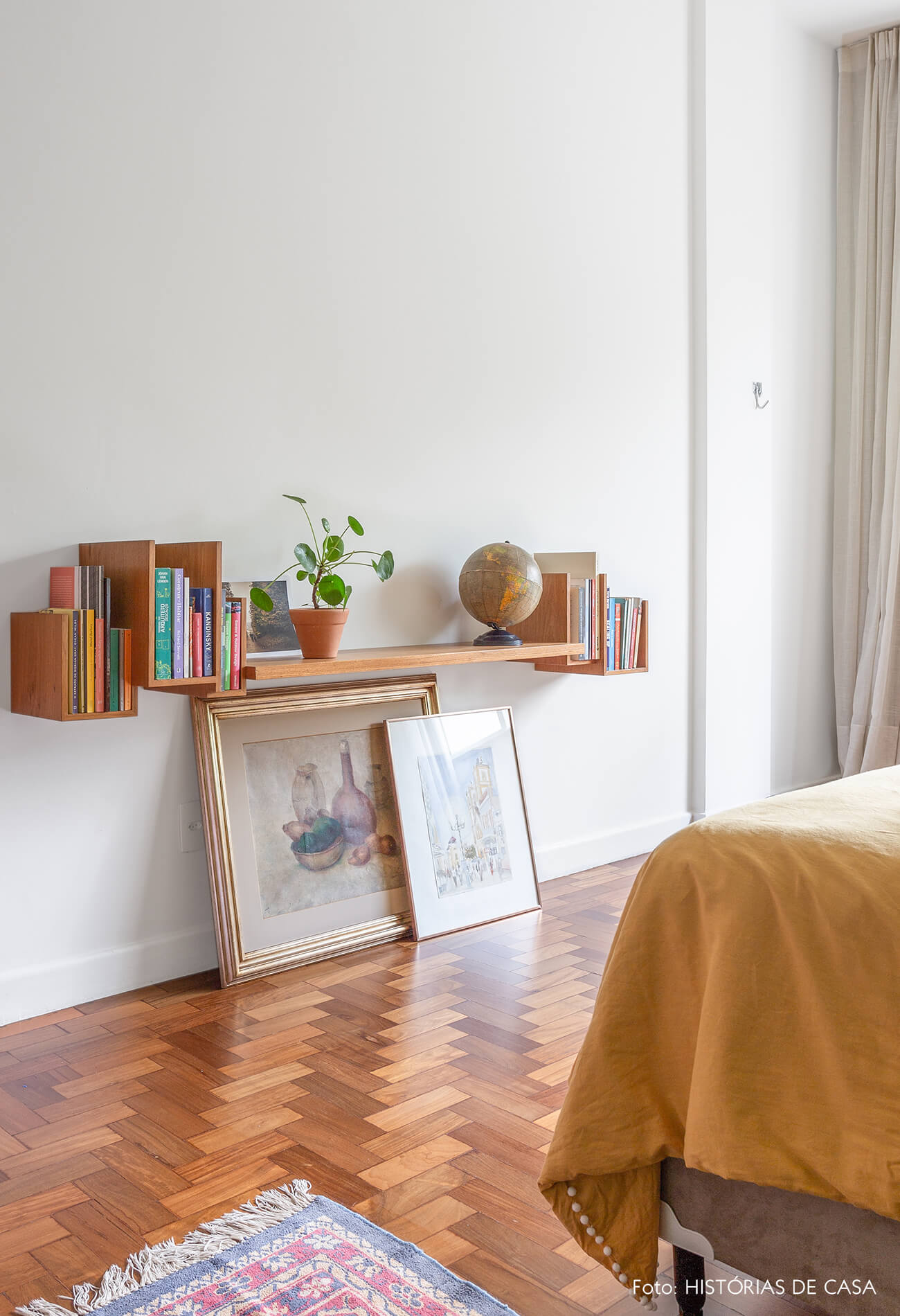 decoração quarto com prateleira de madeira e quadros no chão