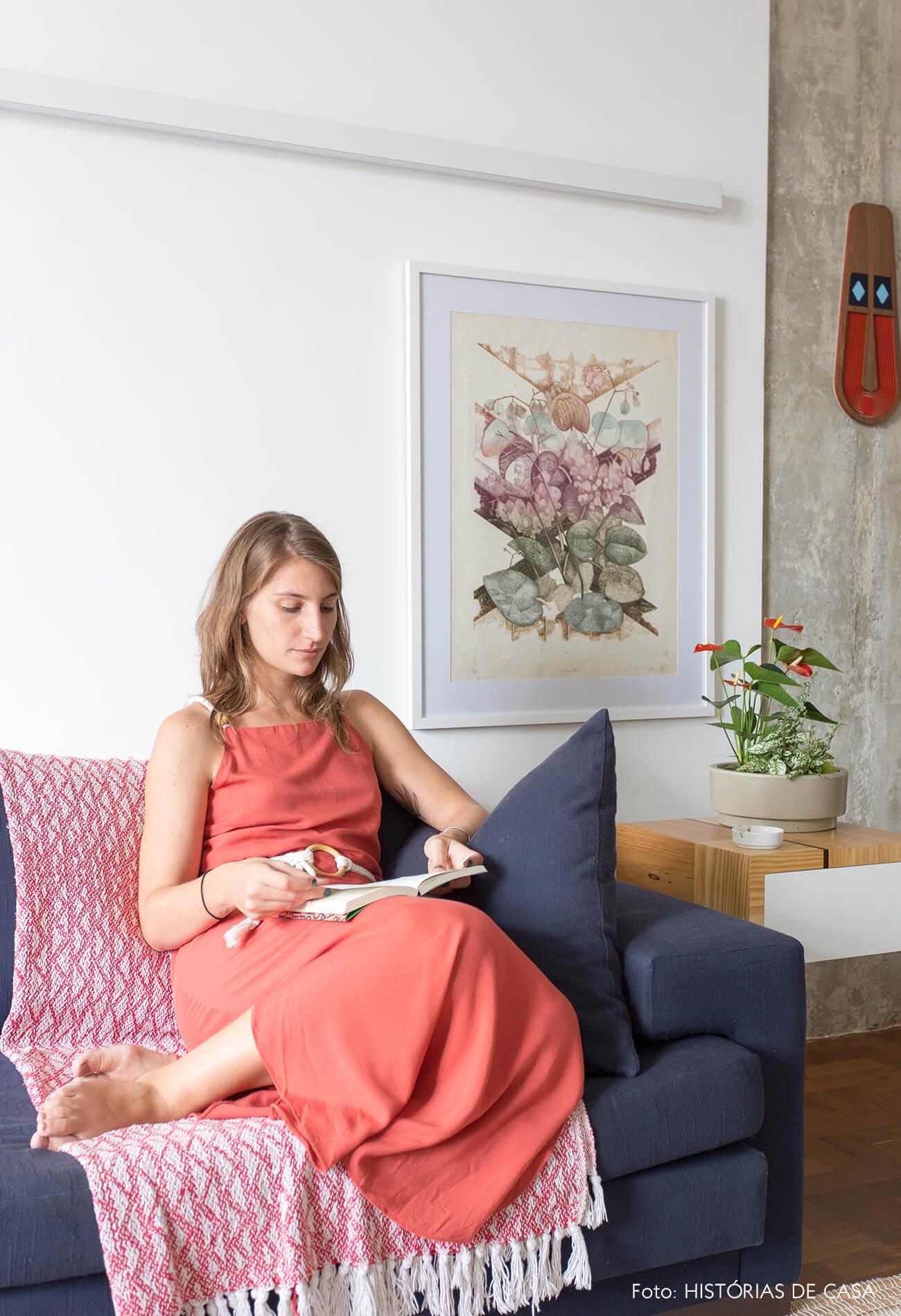 decoração retrato em sala com sofá azul e mesa de madeira