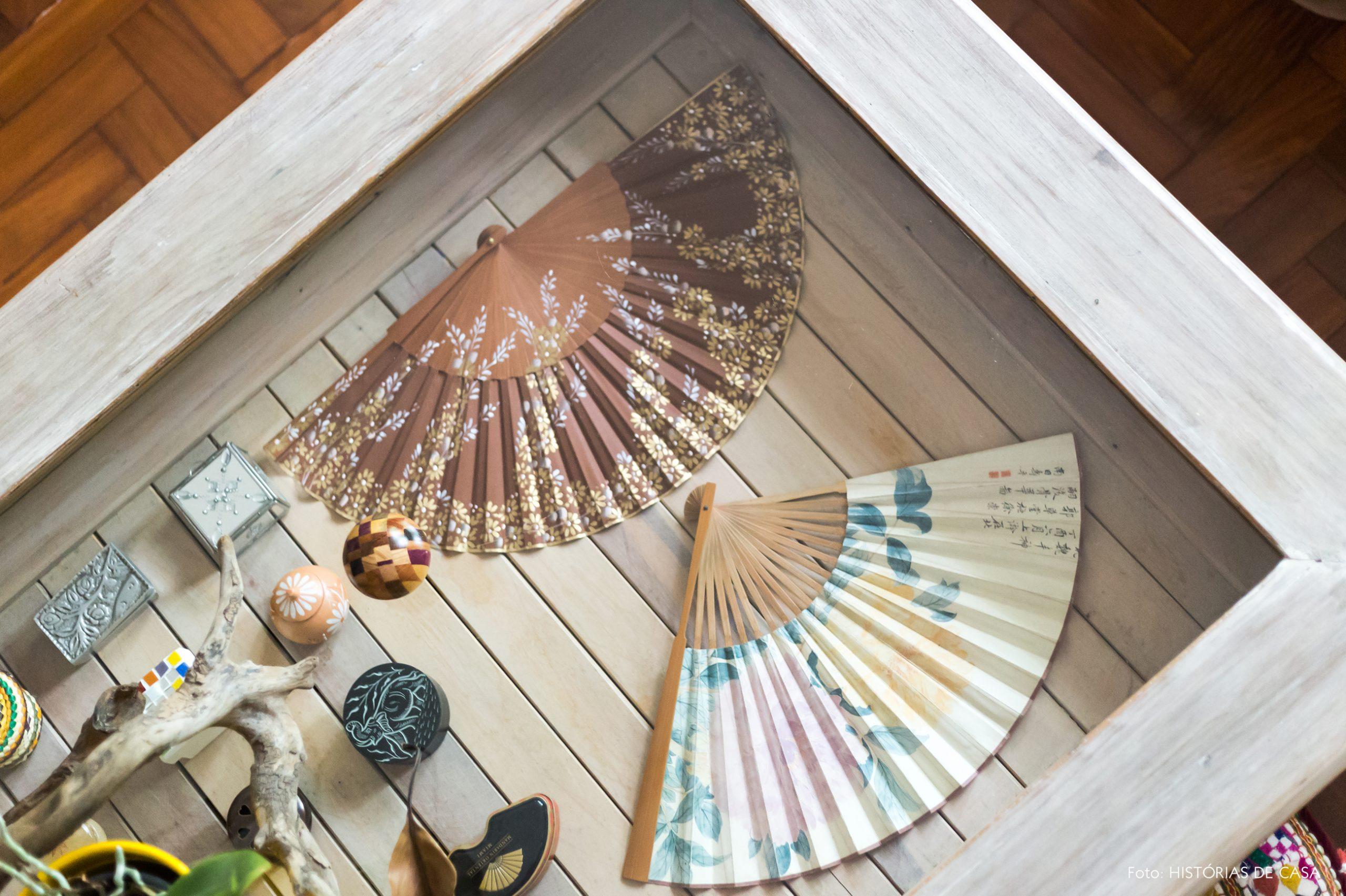 decoração obejtos e leques em mesa de madeira e tampo de vidro