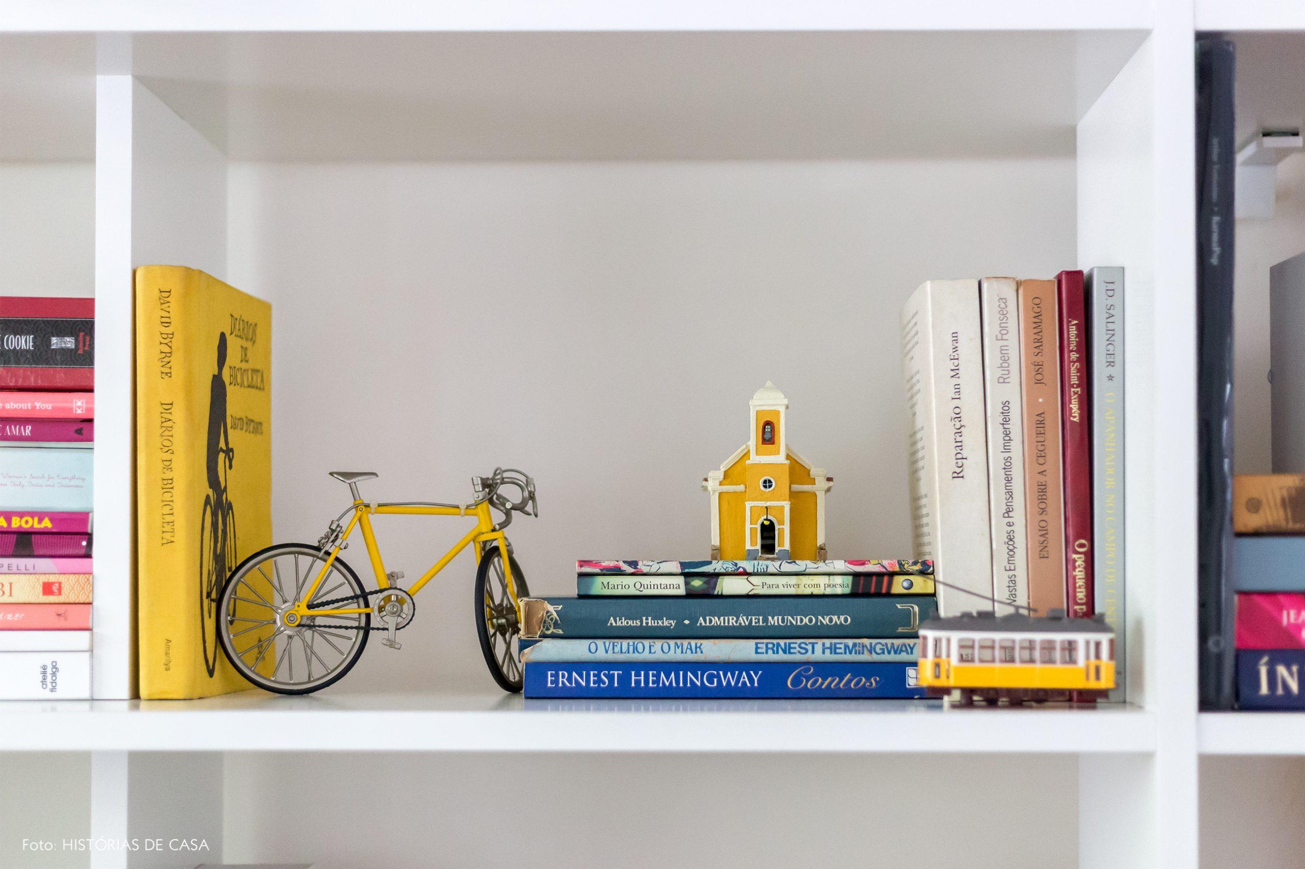 decoração detalhes de livros e objetos em estantes brancas