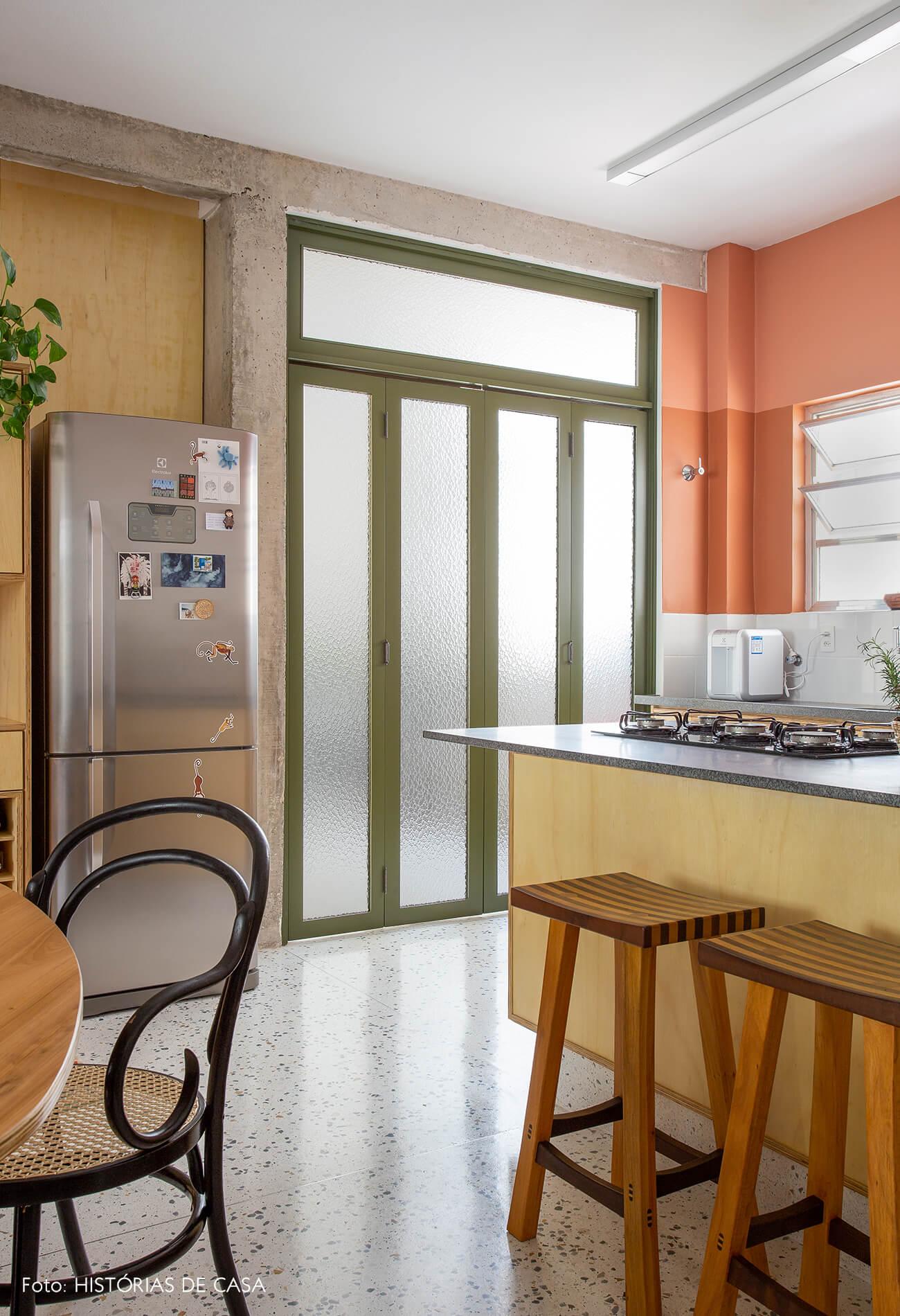 decoração cozinha com parede terrosa, porta serralheria, e cadeira thonet