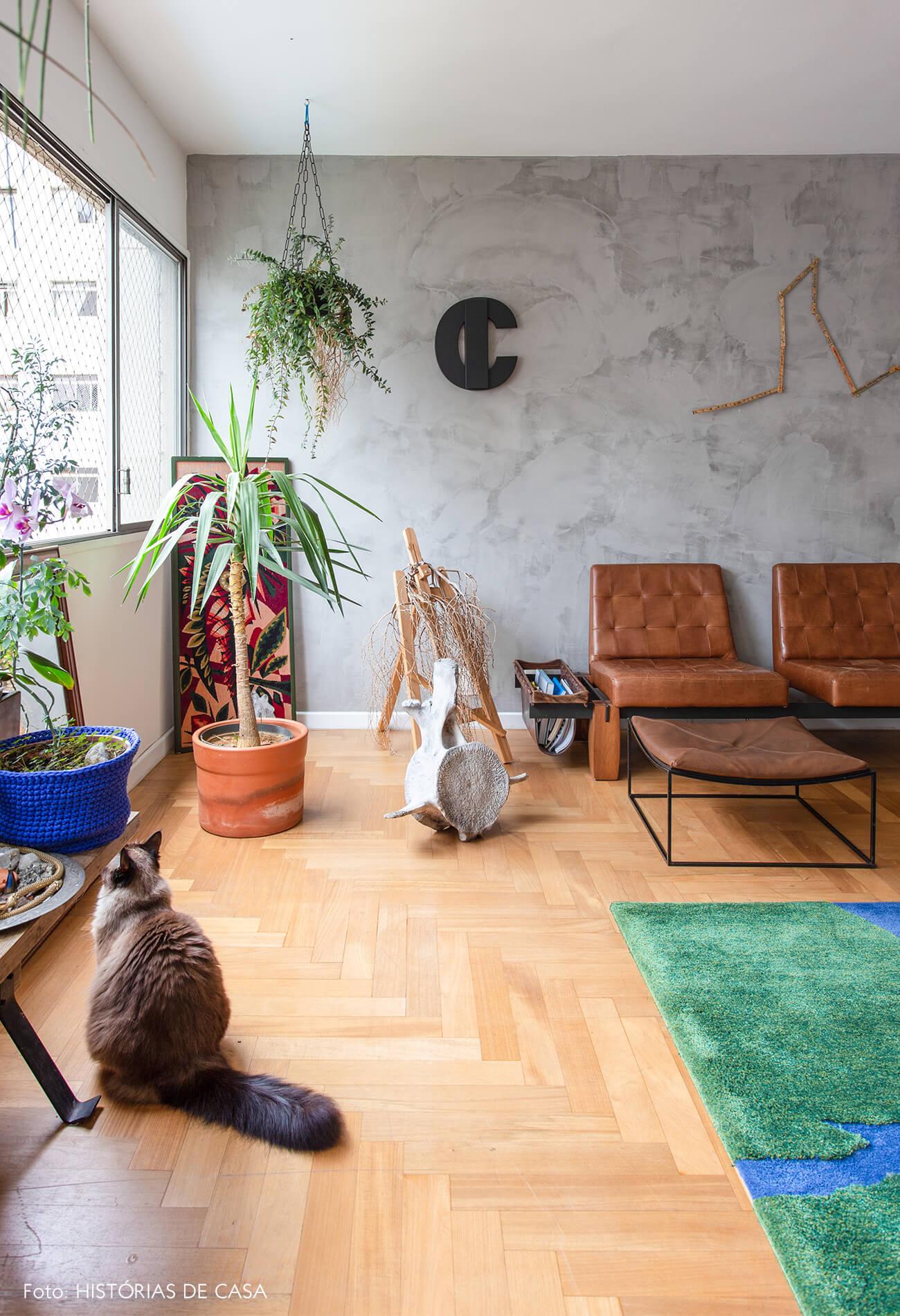decoração sala com parede de cimento queimado plantas e poltrona de couro