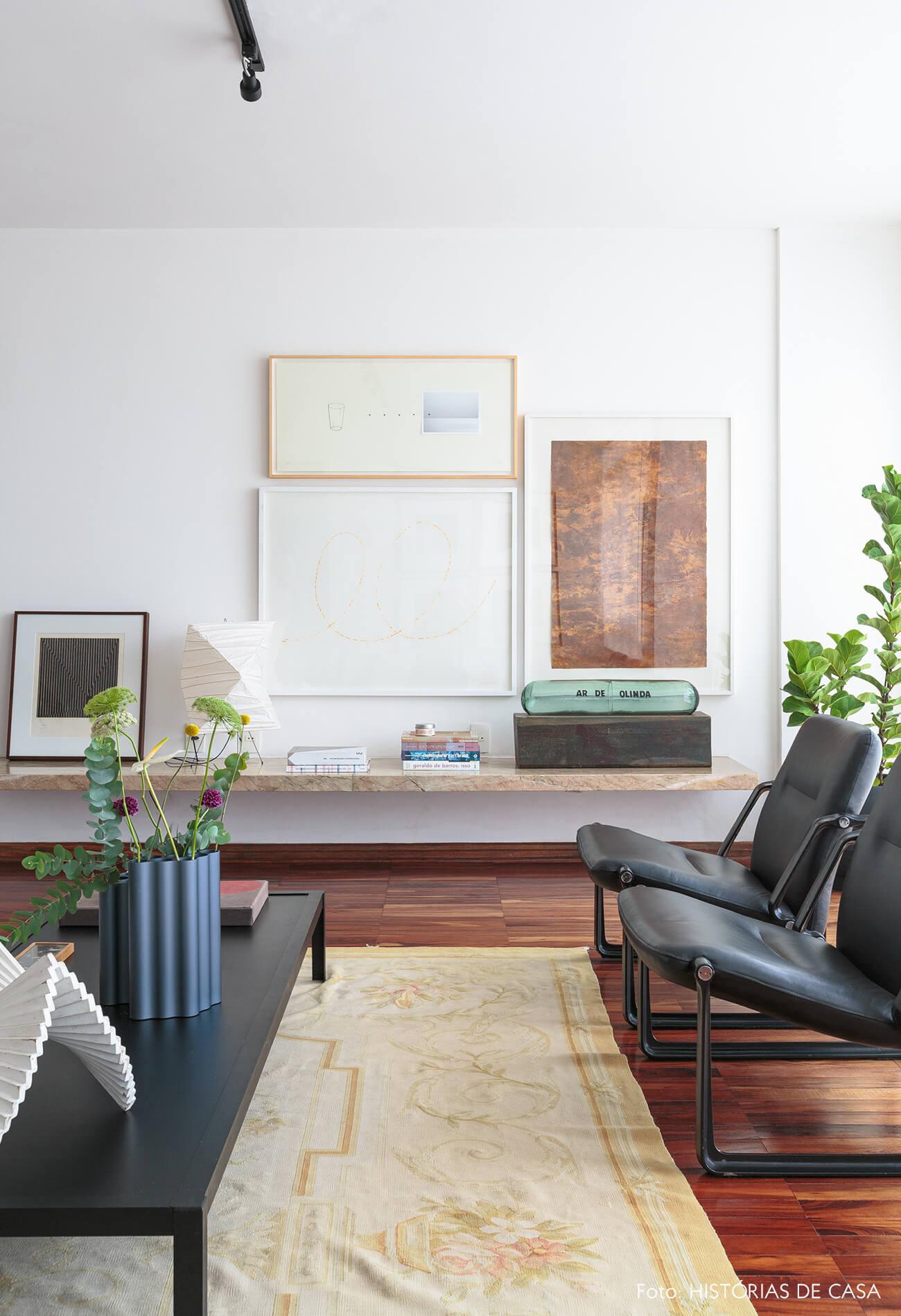 decoração sala com poltronas e mesa de centro pretas e obras de arte