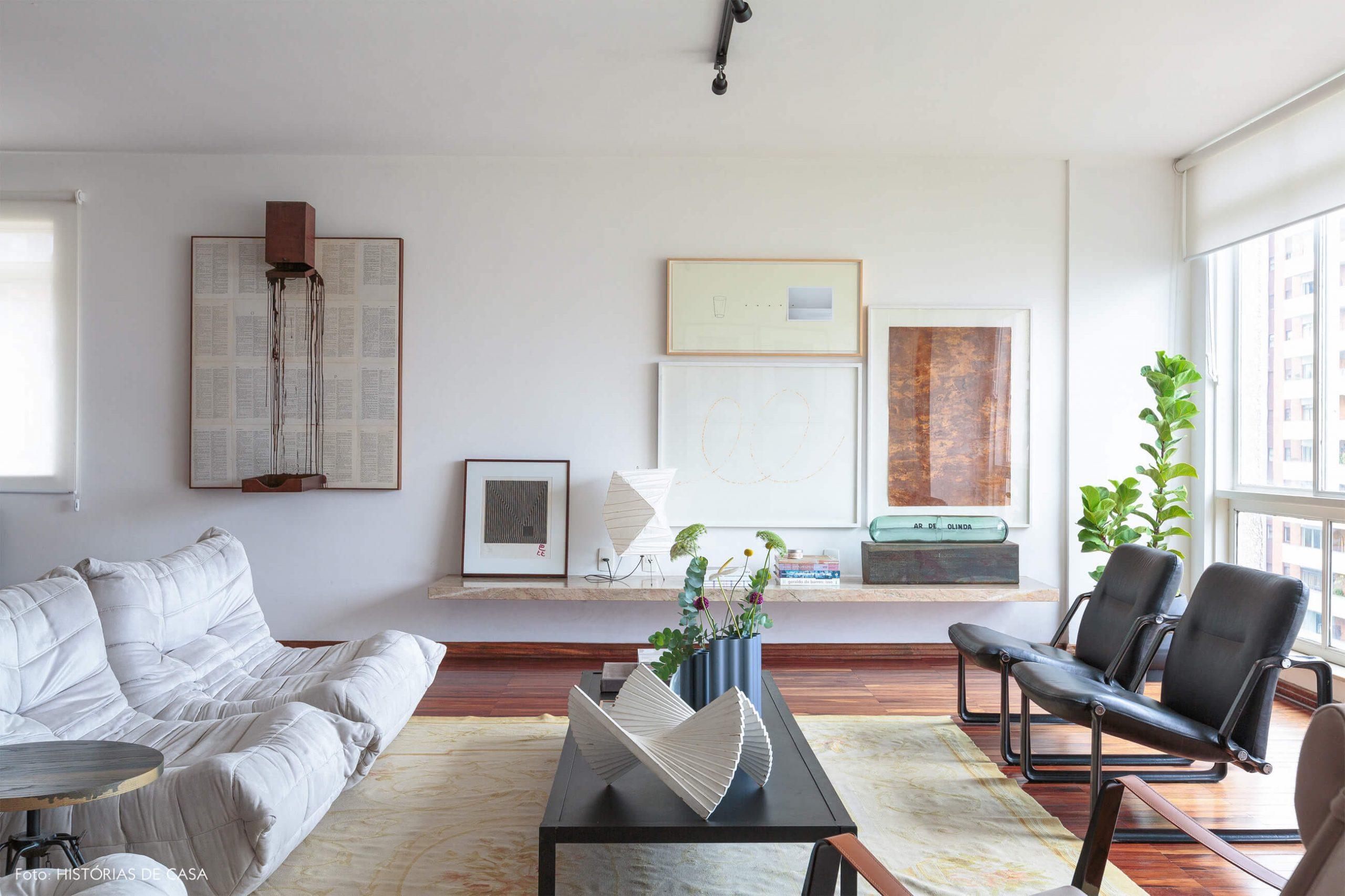 decoração sala bem iluminada com obras de arte e sofá branco