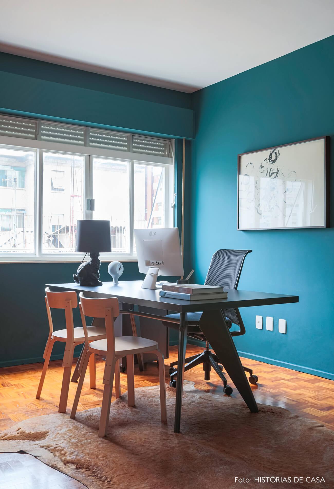 home office com parede azul e cadeiras de madeira
