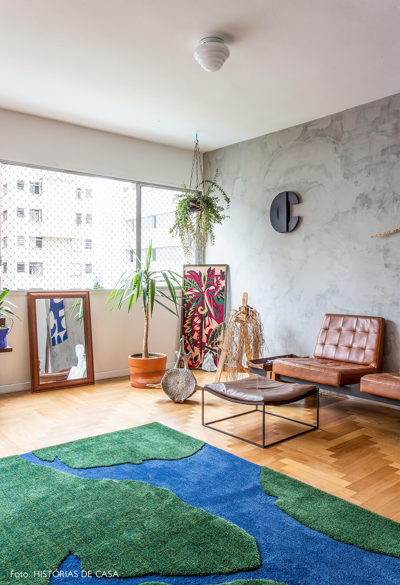decoração sala com parede de cimento queimado poltrona de couso e tapete verde e azul