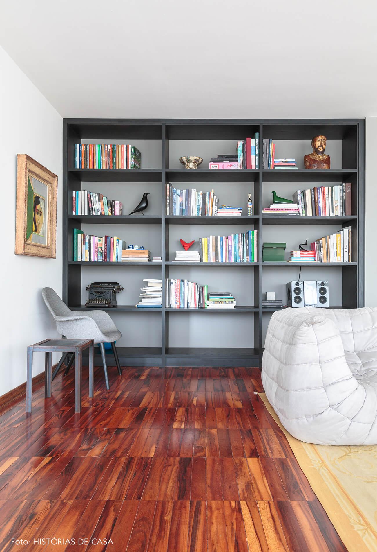 decoração sala com piso de madeira sofá branco e estante preta