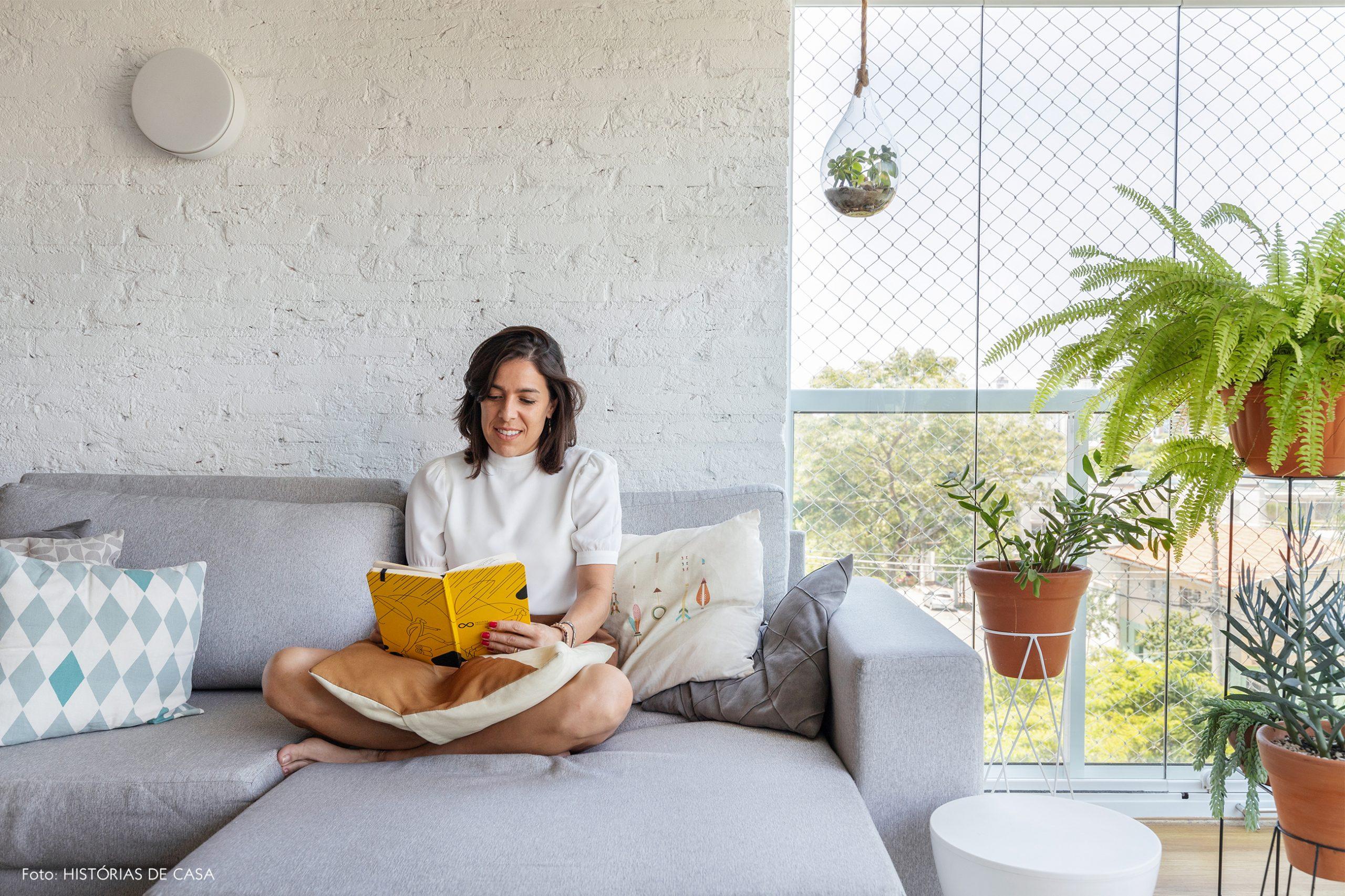 decoração retrato em sala com parede de tijolos brancos, plantas e sofá cinza