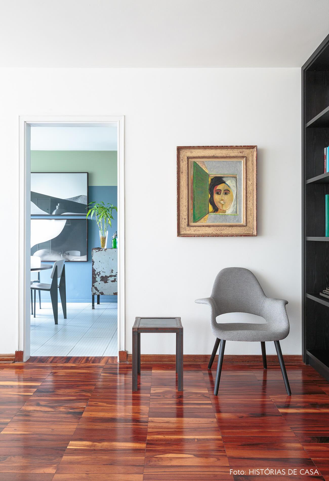 decoração sala com poltrona cinza e piso de madeira