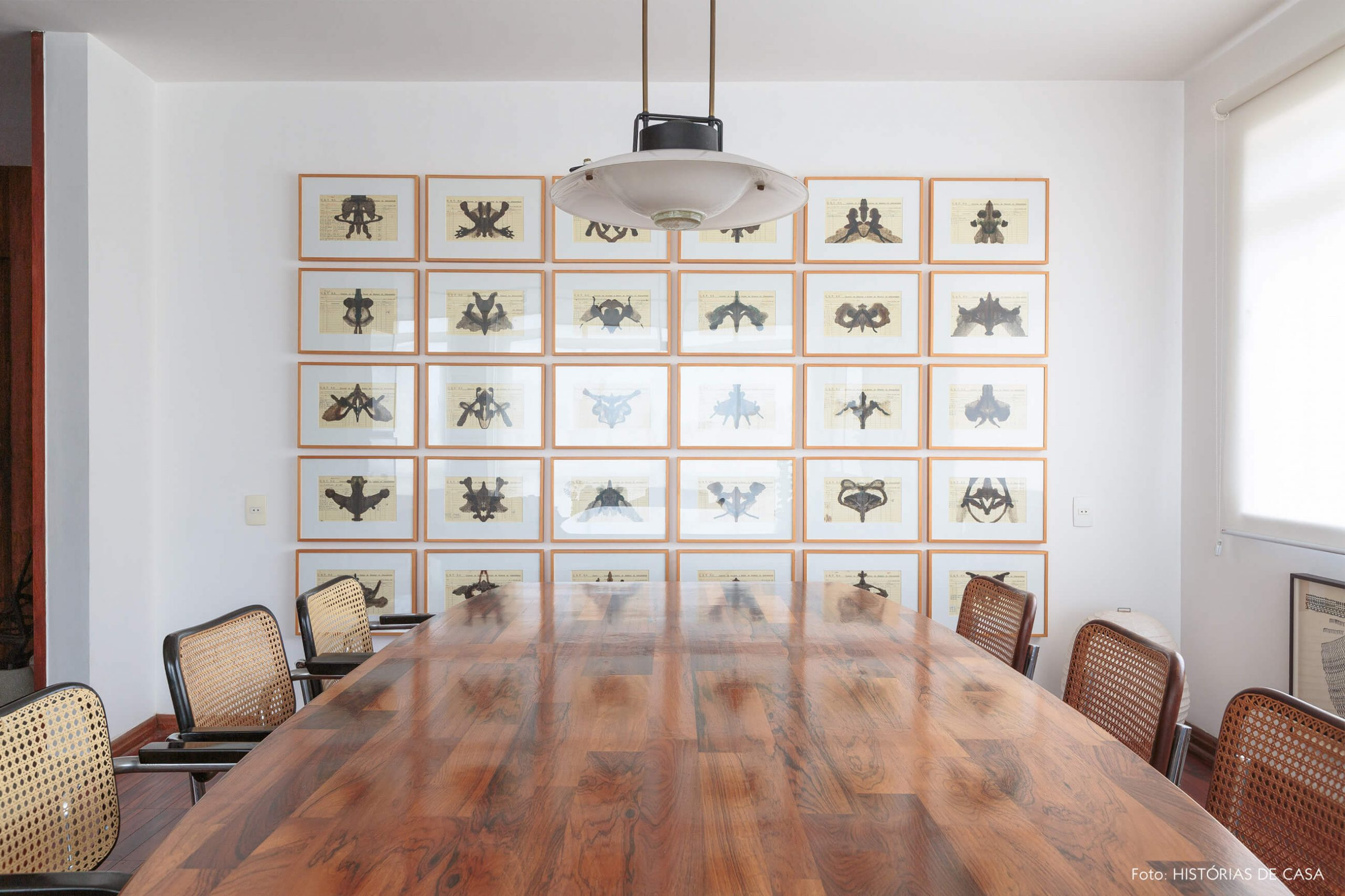decoração sala jantar com cadeira palhinha e obras de arte
