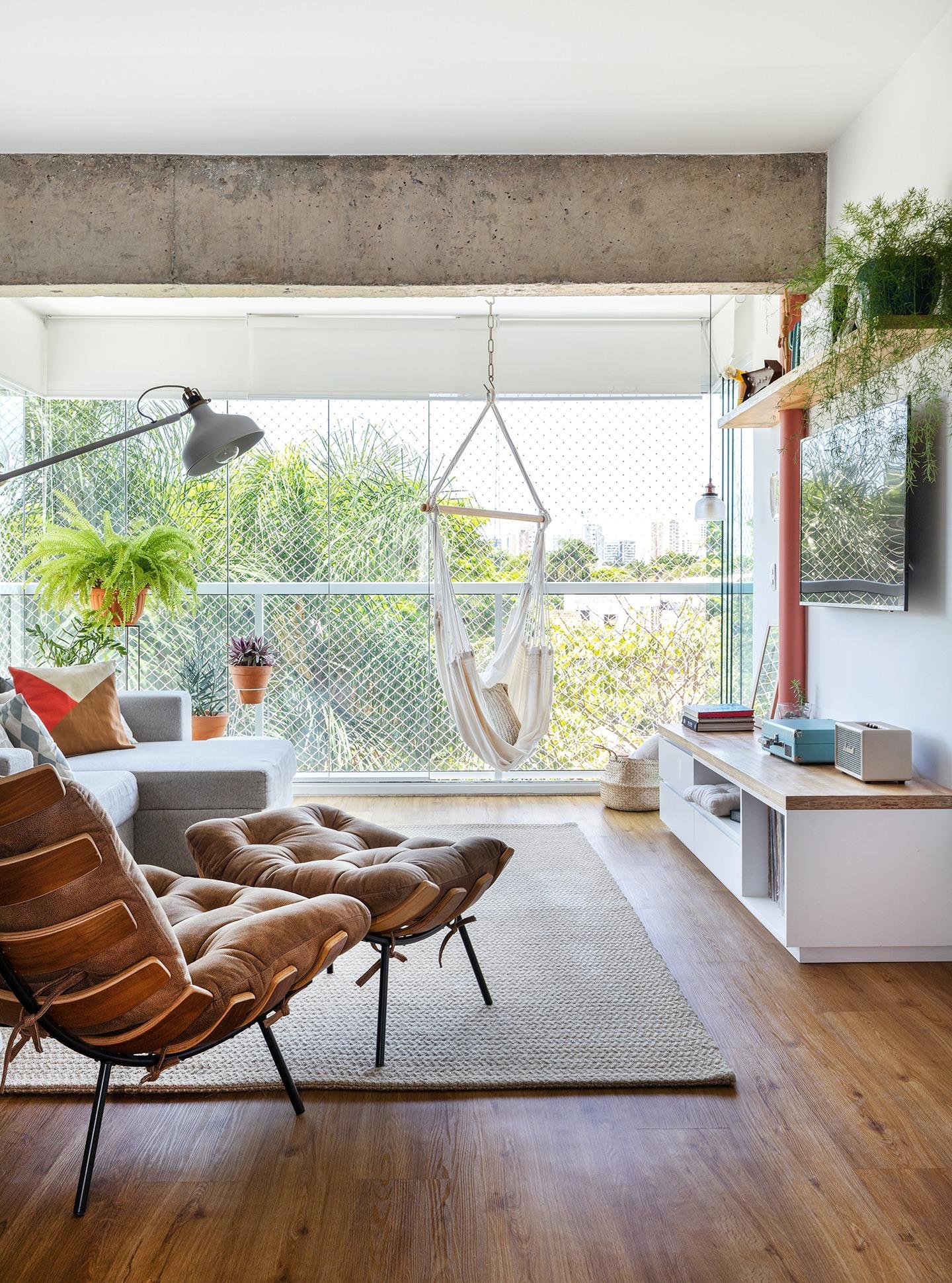 decoração sala com poltrona costela, muitas plantas e poltrona rede