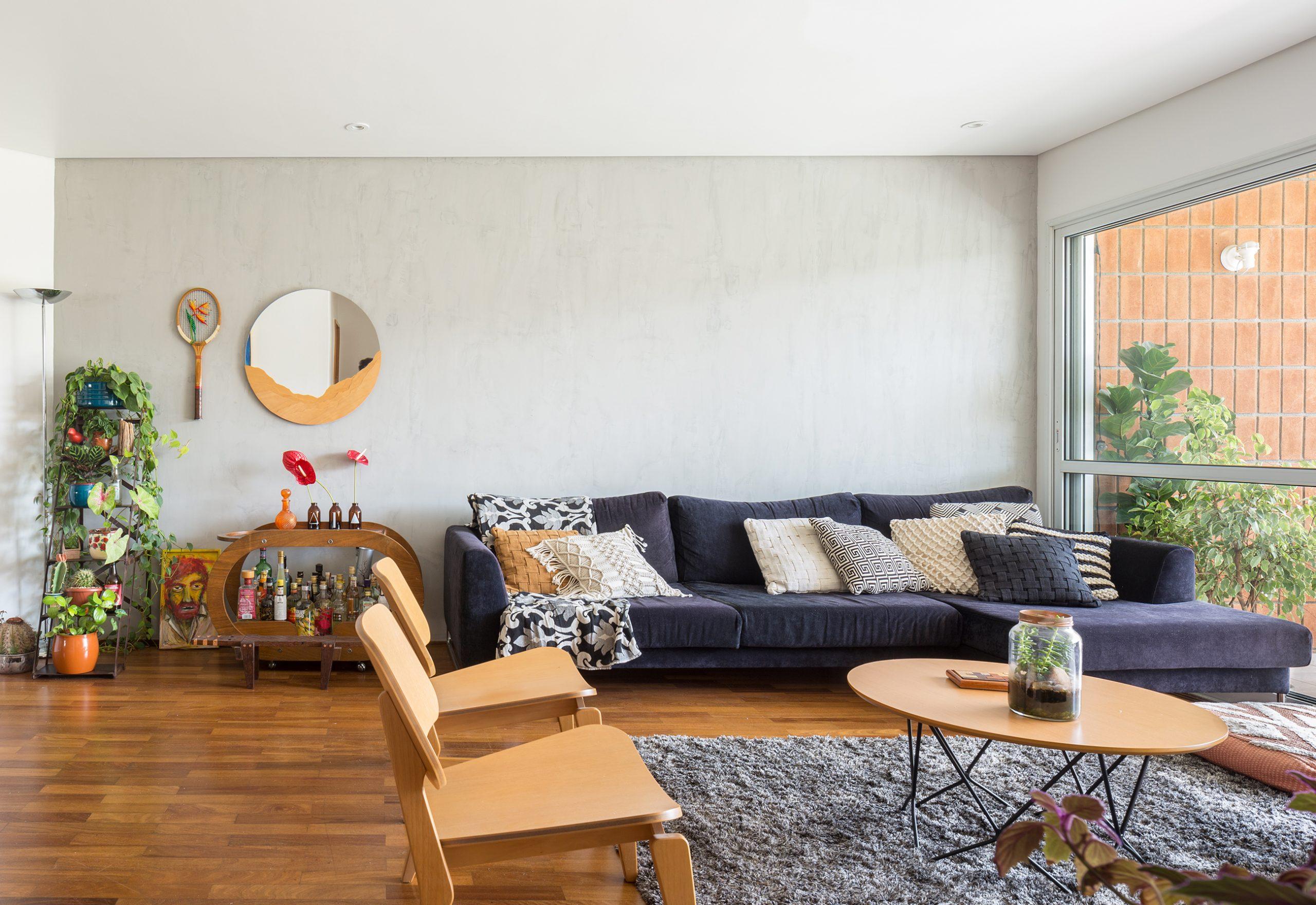 decoração sala com parede cinza cadeira eames e bar de madeira