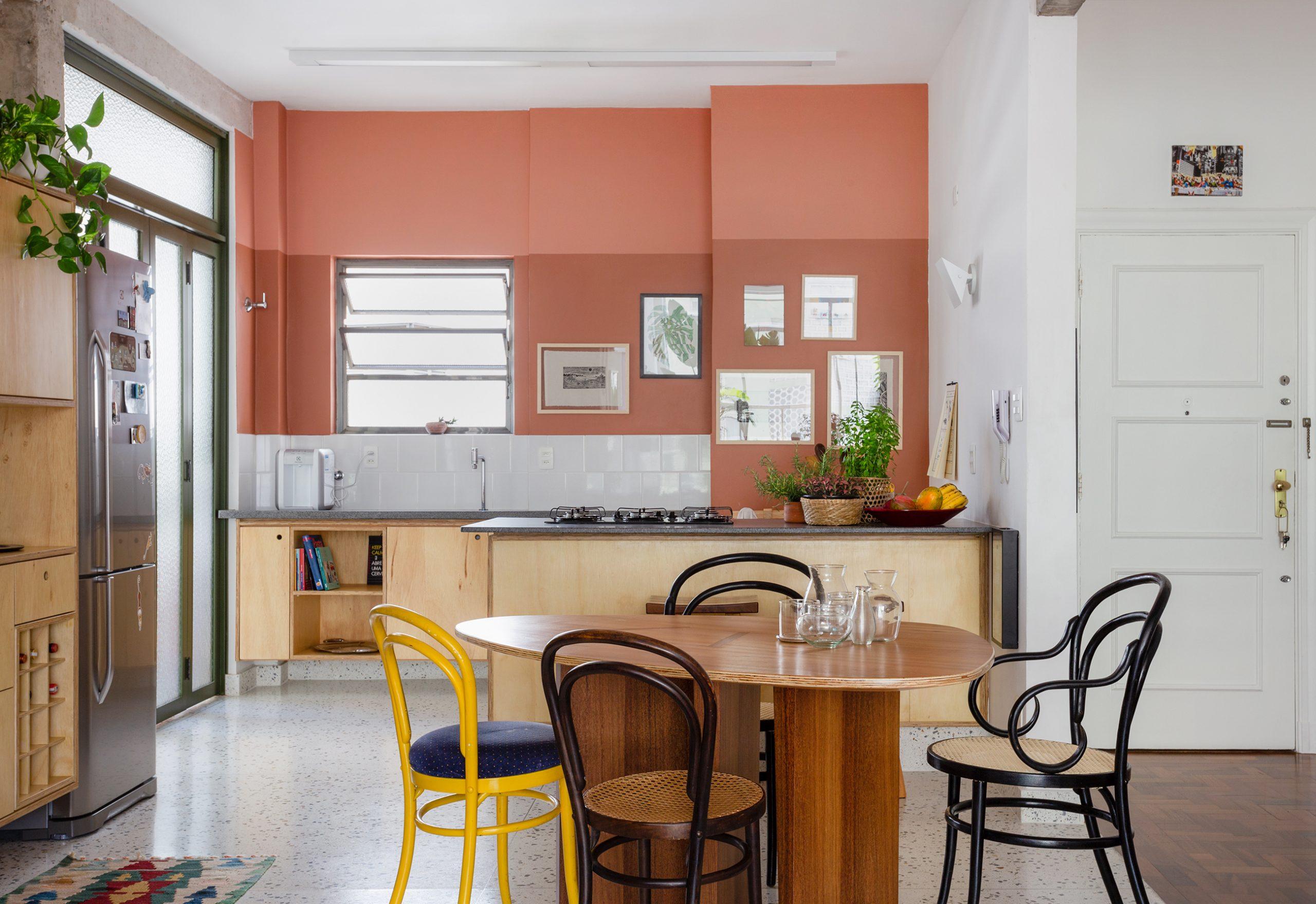 decoração cozinha com parede terrosa, porta serralheria, e cadeira thone