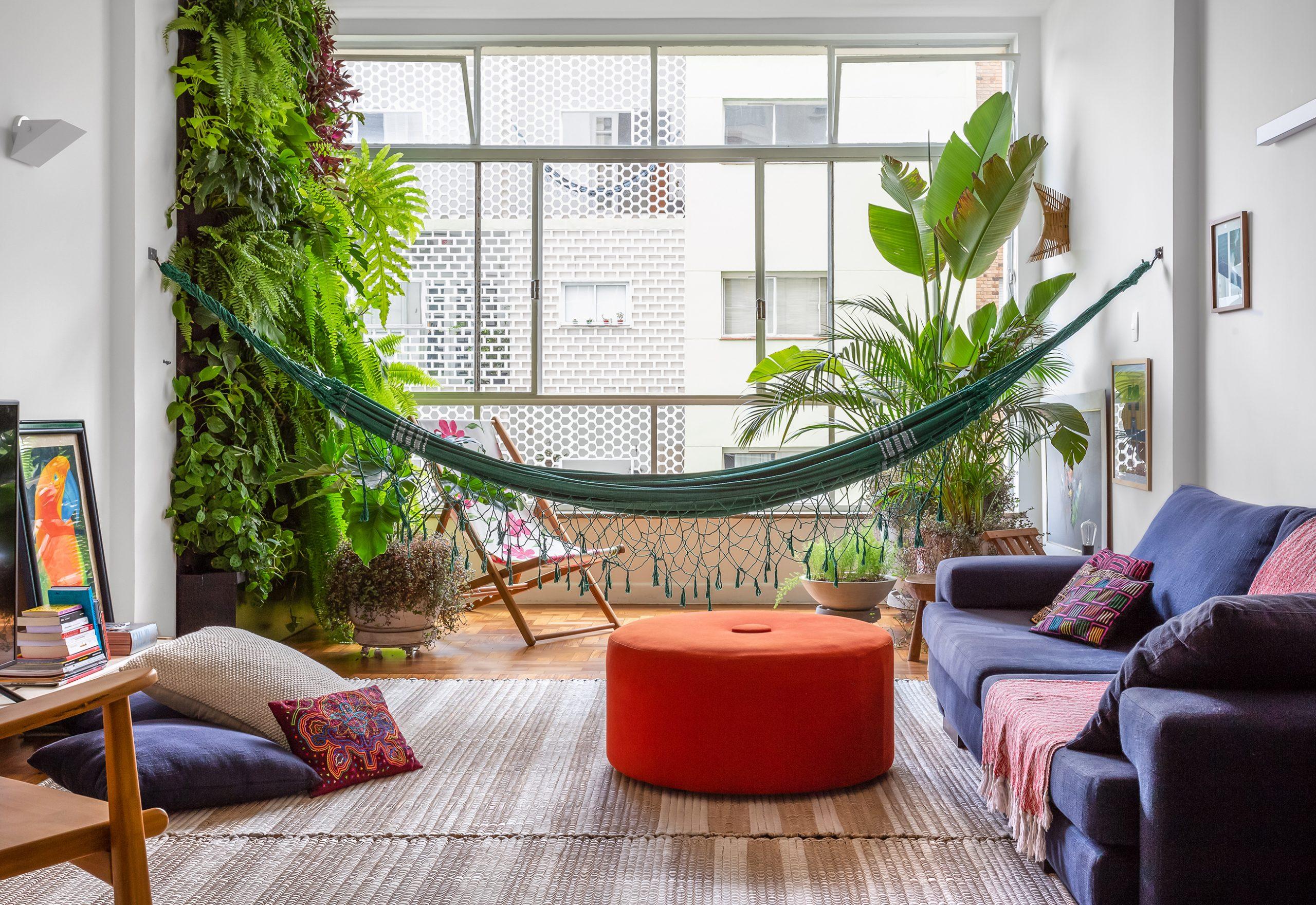 decoração sala com muitas plantas, rede e pufe colorido