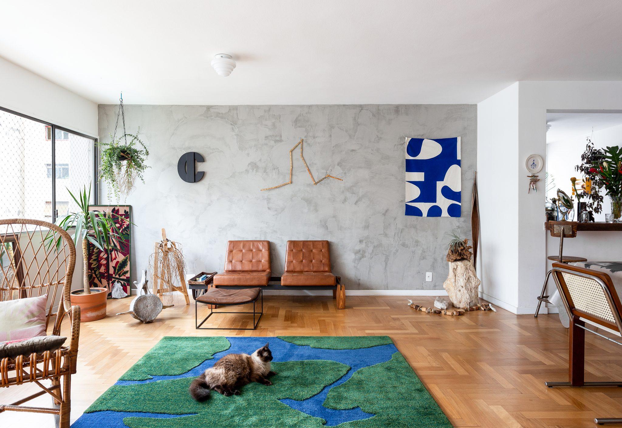 decoração sala de parede de cimento queimado poltronas de couro e tapete verde e azul