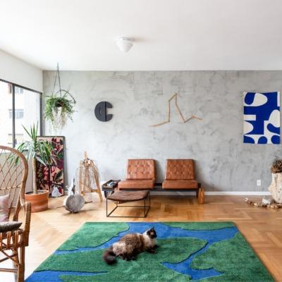 decoração sala com parede de cimento queimado tapete verde e azul e poltrona couro