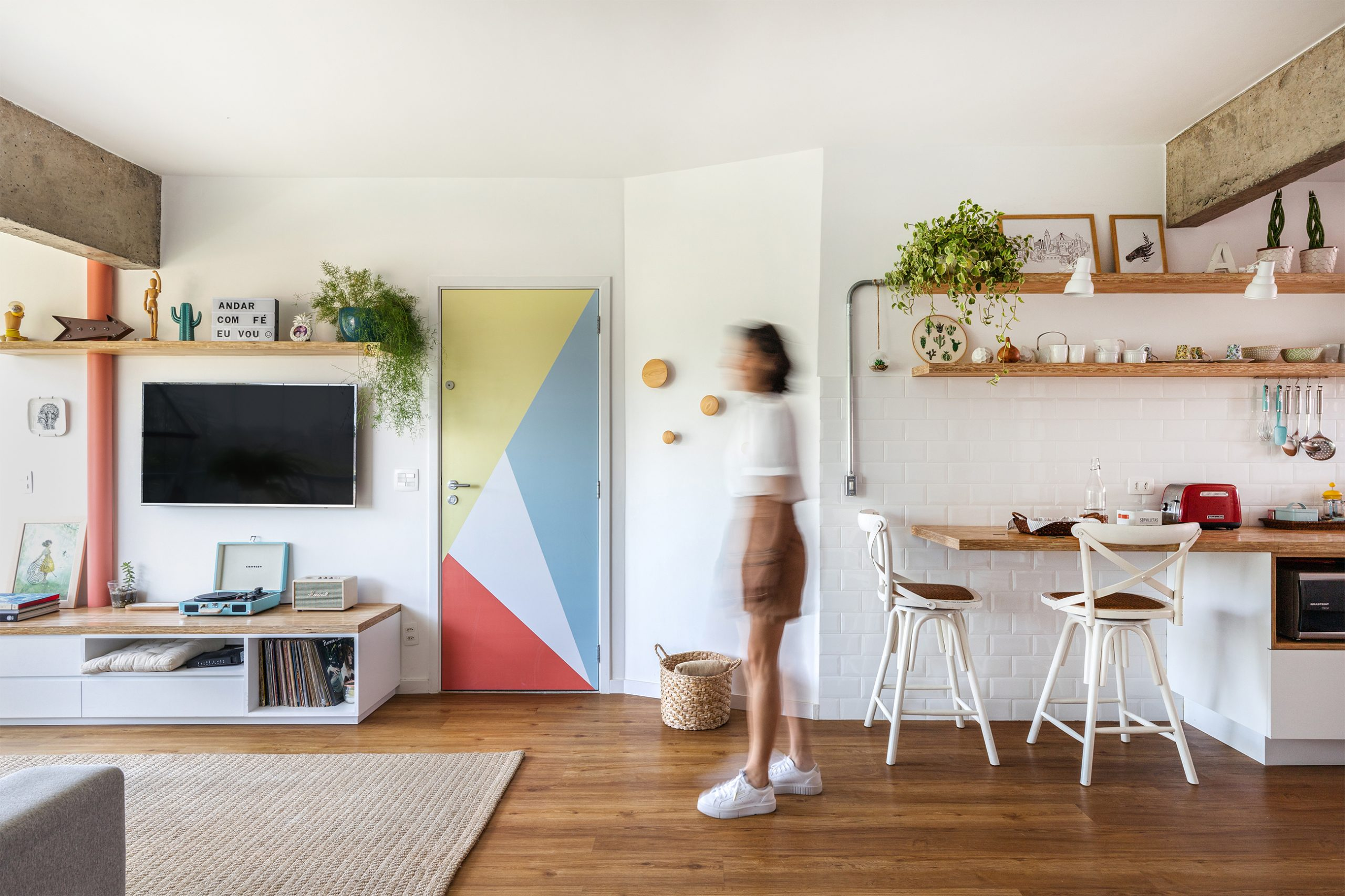 decoração sala com adesivo na porta, cesto e ganchos de madeira