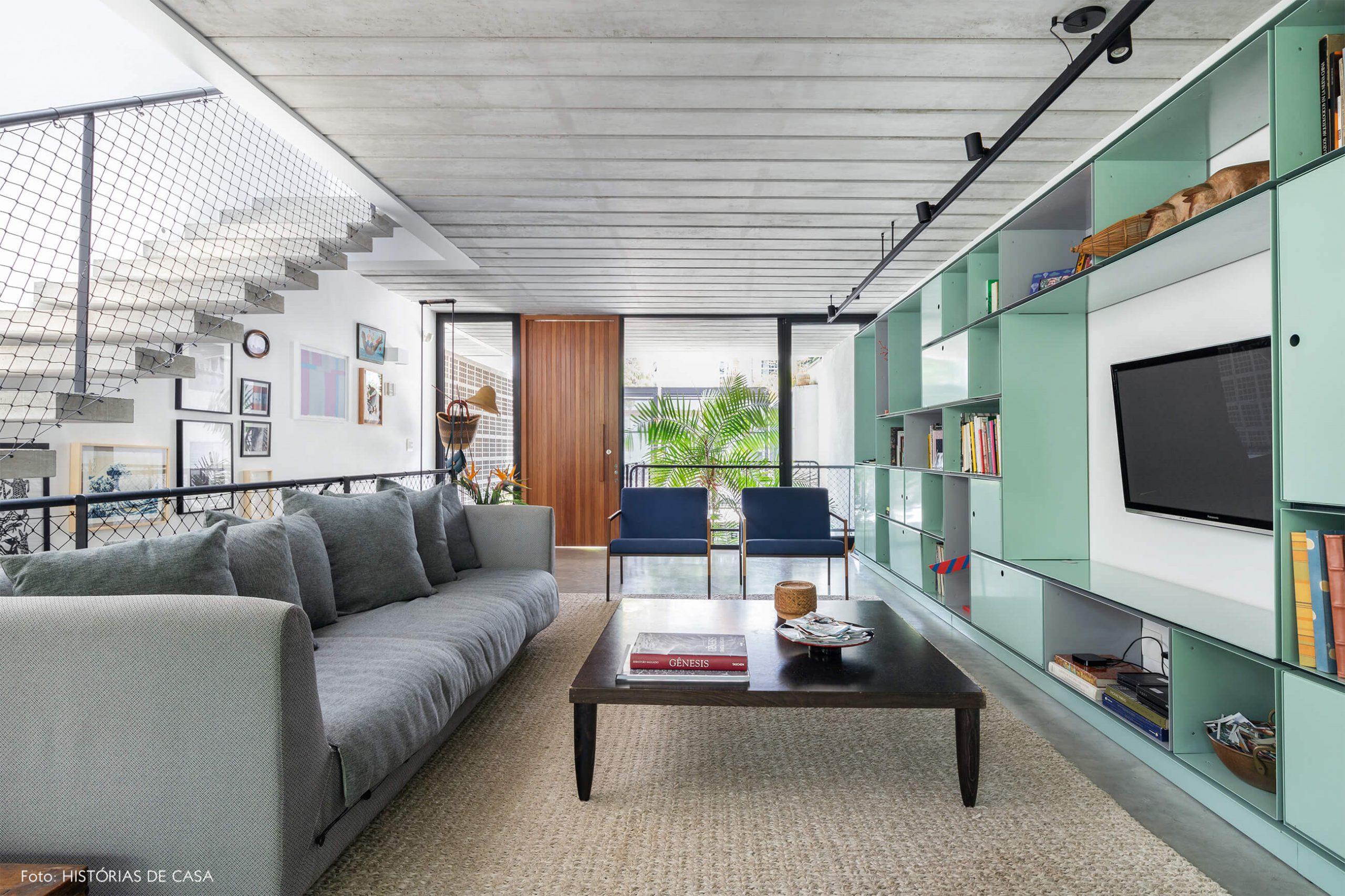 decoração casa sala com estante verde, sofá cinza e mesa de madeira