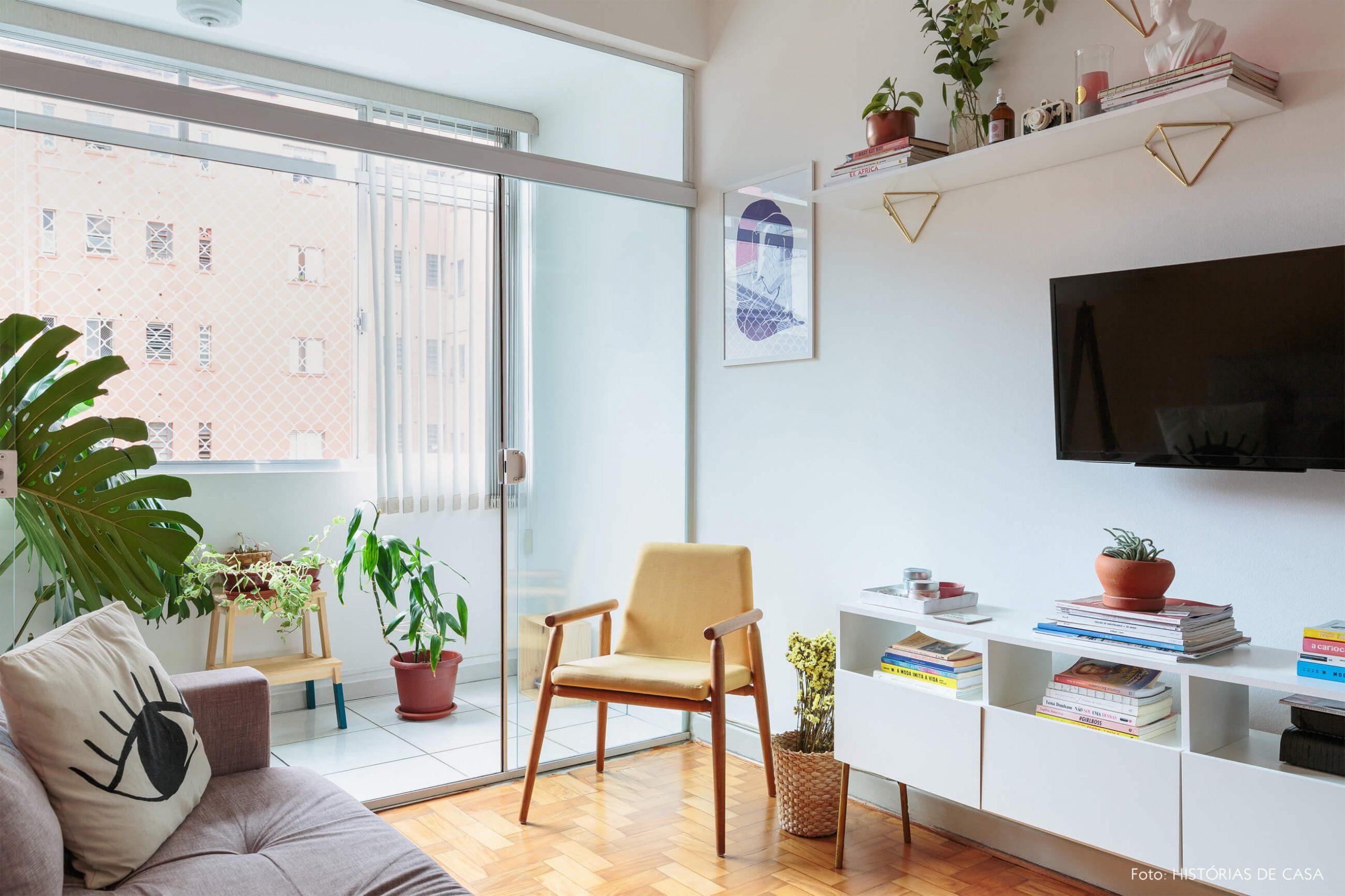 decoração ape alugado sala com poltrona amarela e varanda com plantas