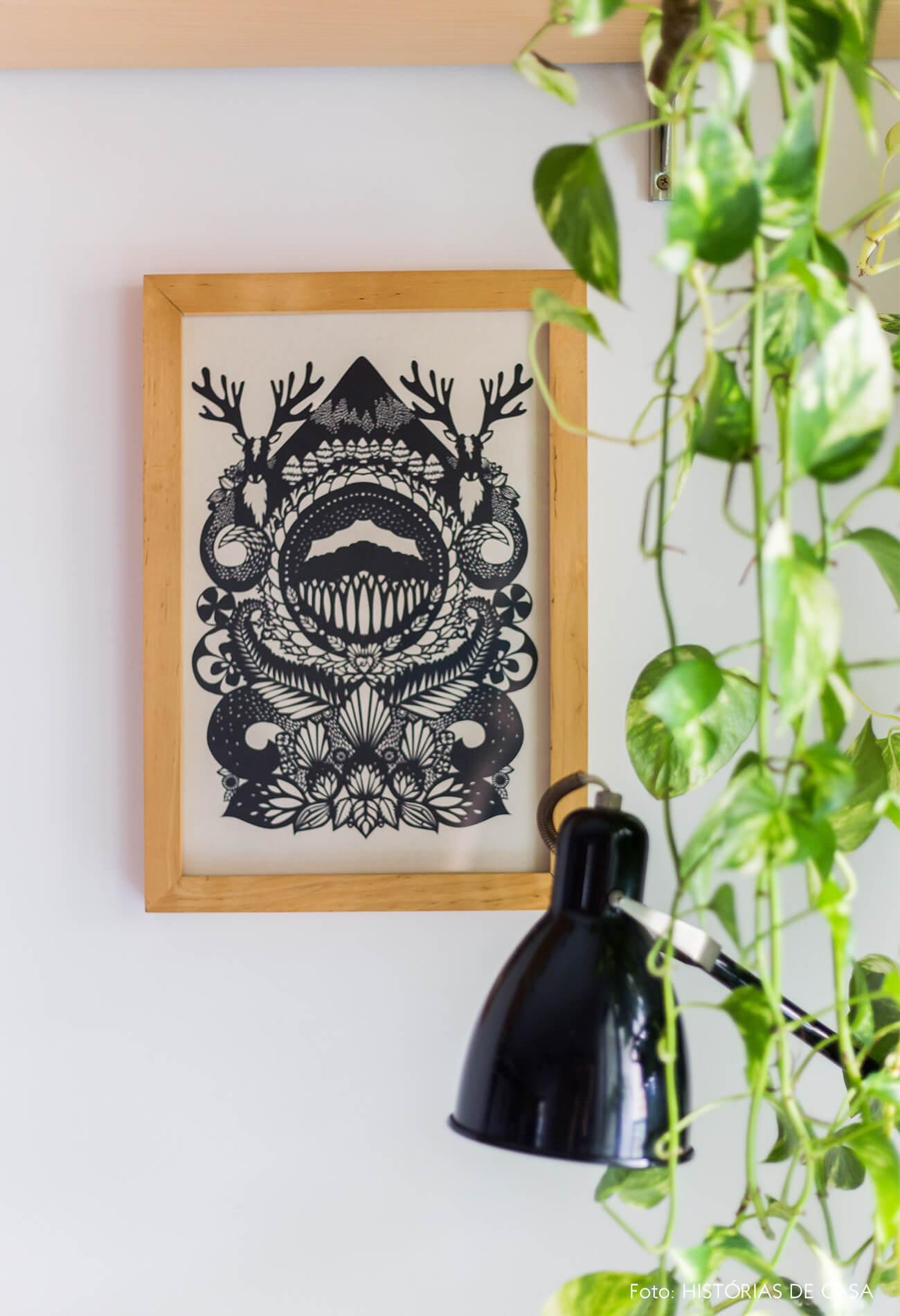 decoração sala com plantas jiboia e quadros com moldura de madeira clara