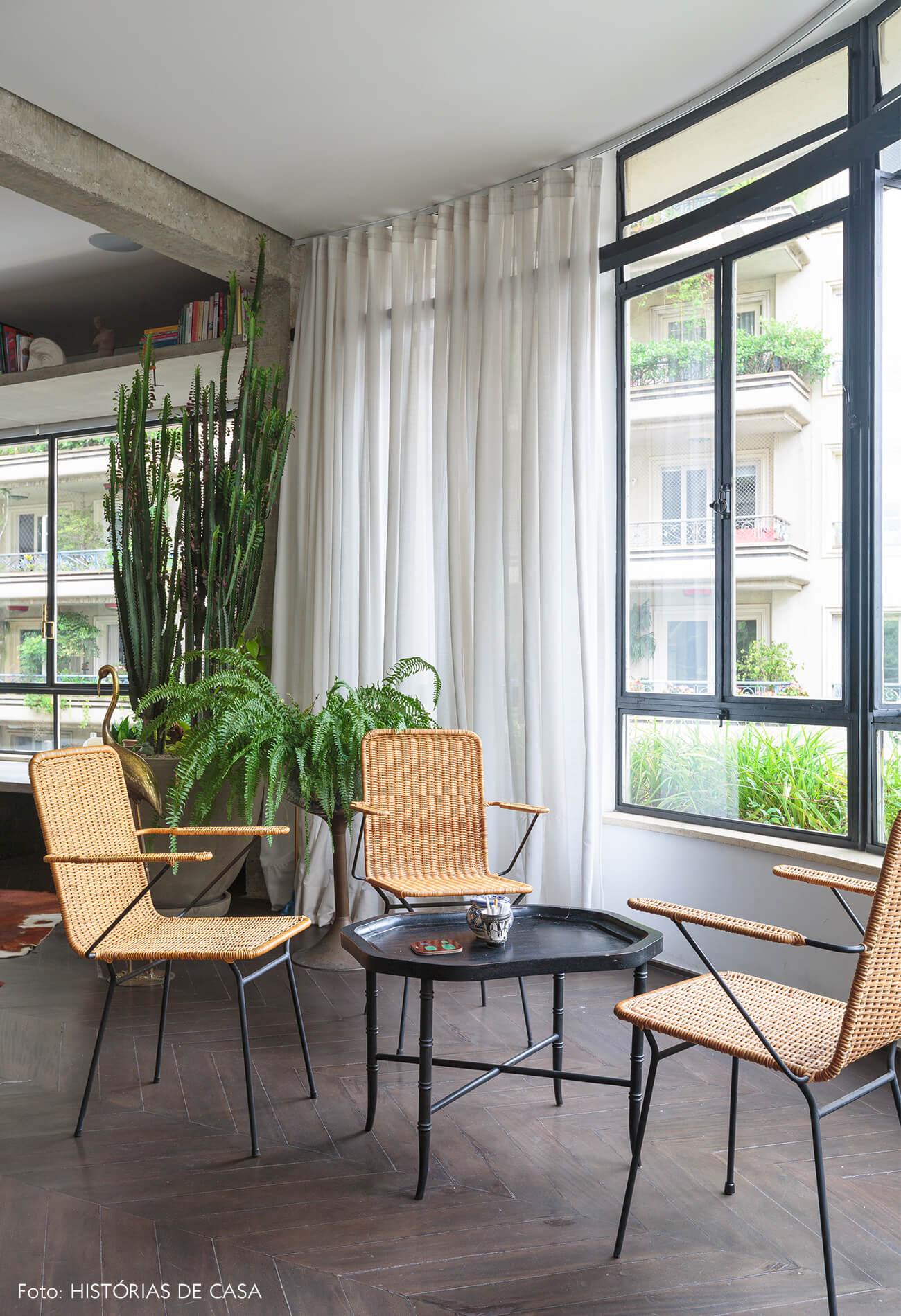 decoração ap sala com cadeiras de palha, plantas e banco de concreto