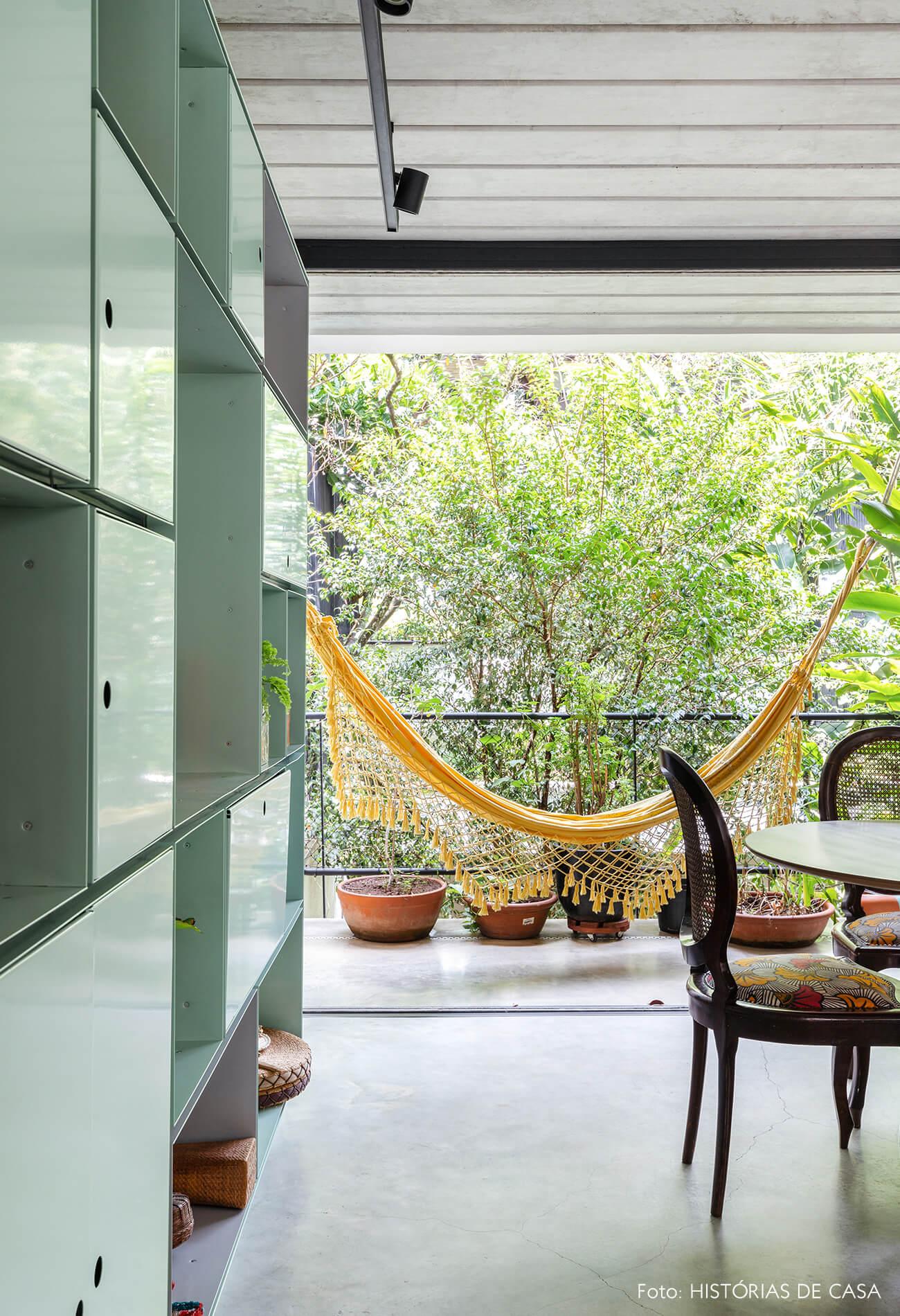 decoração casa sala com estante de metal verde, rede e cadeira de madeira