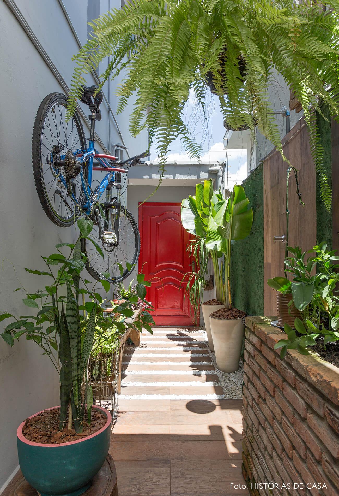 casa decoração hall com muitas plantas e porta vermelha